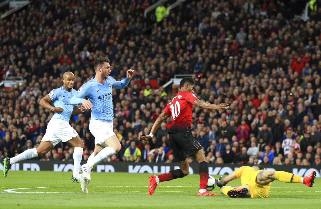 Manchester United's Marcus Rashford, center, challenges Manchester City goalkeeper Ederson, right, during the English Premier League soccer match between Manchester United and Manchester City at Old Trafford Stadium in Manchester, England, Wednesday April 24, 2019. (AP Photo/Jon Super)