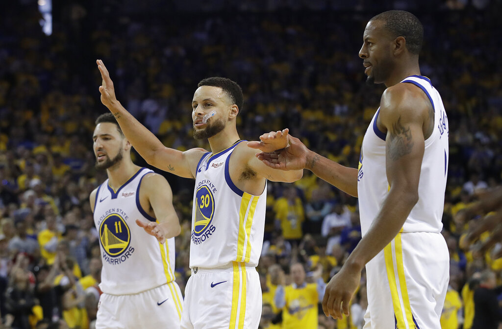Golden State Warriors' Klay Thompson, from left, celebrates with Stephen Curry and Andre Iguodala during the second half of Game 1 of a second-round NBA basketball playoff series against the Houston Rockets in Oakland, Calif., Sunday, April 28, 2019. (AP Photo/Jeff Chiu)