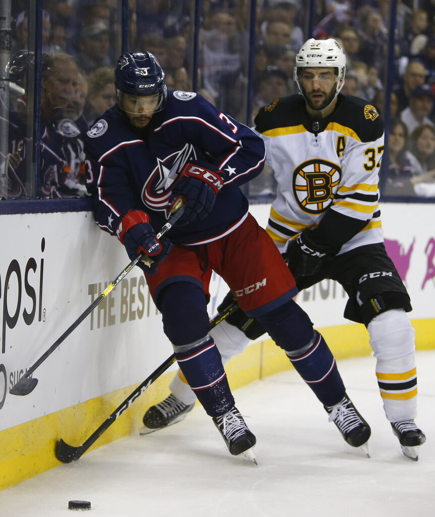 Columbus Blue Jackets' Seth Jones, left, controls the puck on front of Boston Bruins' Patrice Bergeron during the third period of Game 3 of an NHL hockey second-round playoff series Tuesday, April 30, 2019, in Columbus, Ohio. The Blue Jackets beat the Bruins 2-1. (AP Photo/Jay LaPrete)