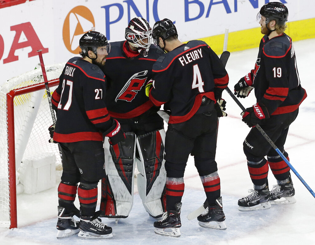 Carolina Hurricanes goalie Curtis McElhinney is congratulated by Justin Faulk (27), Haydn Fleury (4) and Dougie Hamilton (19) following the Hurricanes' 5-2 win over the New York Islanders in Game 3 of an NHL hockey second-round playoff series in Raleigh, N.C., Wednesday, May 1, 2019. (AP Photo/Gerry Broome)