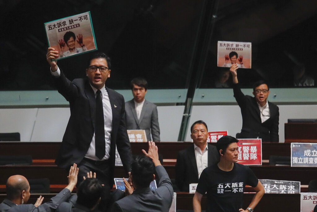 Security officials try to stop pro-democracy lawmakers who shout a slogan as Hong Kong's Chief Executive Carrie Lam delivers a speech at chamber of the Legislative Council in Hong Kong Wednesday, Oct. 16, 2019.  Photo courtesy of AP Photo/Kin Cheung. Thumbnail photo courtesy of AP Photo/Mark Schiefelbein.