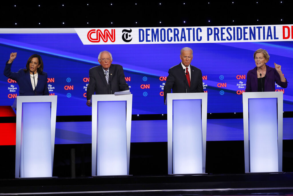 From left, Democratic presidential candidate Sen. Kamala Harris, D-Calif., Sen. Bernie Sanders, I-Vt., former Vice President Joe Biden, and Sen. Elizabeth Warren, D-Mass., participate in a Democratic presidential primary debate hosted by CNN/New York Times at Otterbein University, Tuesday, Oct. 15, 2019, in Westerville, Ohio.  Photos courtesy of AP Photo/John Minchillo.
