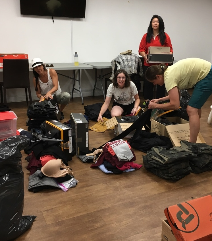 SUMMER 2016 - ABOVE -  Some of our volunteers sorting through the generous donation from CCI Entertainment