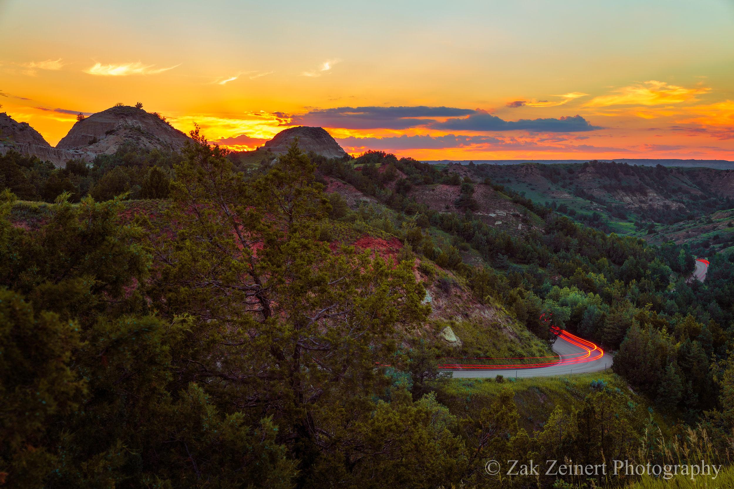 The sun sets behind Scoria Point overlook on the 36-mile park loop