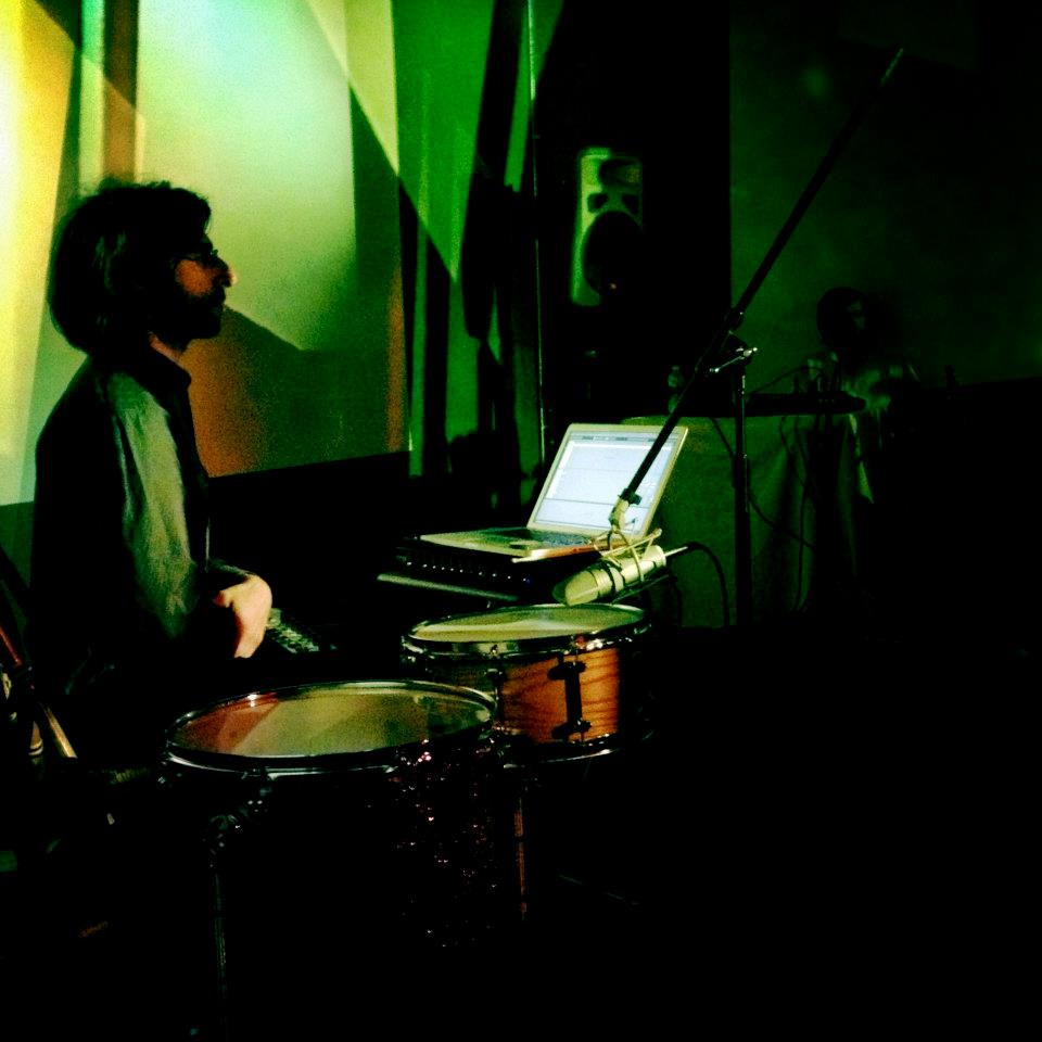 Thursday July 12th  8PM   $10    Drums and Drones   is the solo project of   Brian Chase   ( Yeah Yeah Yeahs / John Zorn) and is performed in conjunction with the stunning visuals of video artist   Ursula Scherrer  . The project uses drums and percussion as a medium for 'going inside the sound:' that of constructing expansive soundscapes, like aural snapshots of tone, to uncover the richness of sonic depth hidden within the resonance of these instruments. Similarly, the visual component investigates and reconstructs elements of found forms, whether in filmed objects or simply light itself. In the live video projections, an architectural abstraction continues to emerge and re-evolve, and layers stack to reveal shifting fields of depth and perception. Drums and Drones credits initial inspiration to La Monte Young and Marian Zazeela's legendary Dream House installation in TriBeCa, NYC.    Evan Miller   is a percussionist and improviser based in Dayton, OH. He works with percussion, found objects, cassette tapes, and field recordings to create music drawing equally from drone and free improvisation. Evan is also a member of Neutrals, an experimental percussion duo, with Andrew Seivert.  http://evanmillerperc.com    Sarah Hughes  is an alto saxophonist, composer, and music educator from Pasadena, Maryland. She is a free improviser who enjoys creating within and on top of many genre frameworks including jazz, swing, blues, folk pop, and rock. Sarah has toured Sweden as part of their first annual Women in Jazz Festival, and has shared the bill, opening for great free improvisers such as Joe Morris, Nicole Mitchell, Fay Victor, William Parker, Hamid Drake, and Ken Vandermark. She also serves as adjunct faculty at Towson University and McDaniel College.  http://www.sarahmariehughes.com