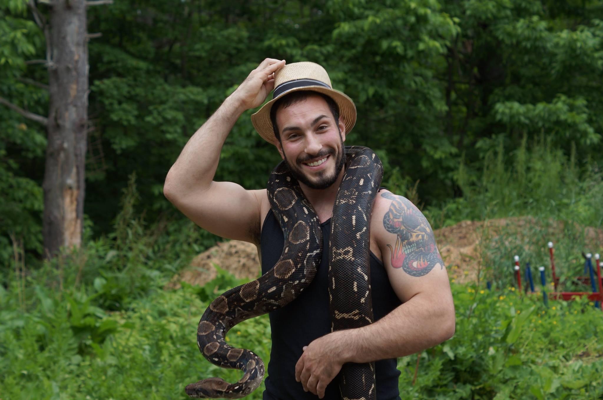 Jason Raimondi steps off set with one of his snakes.