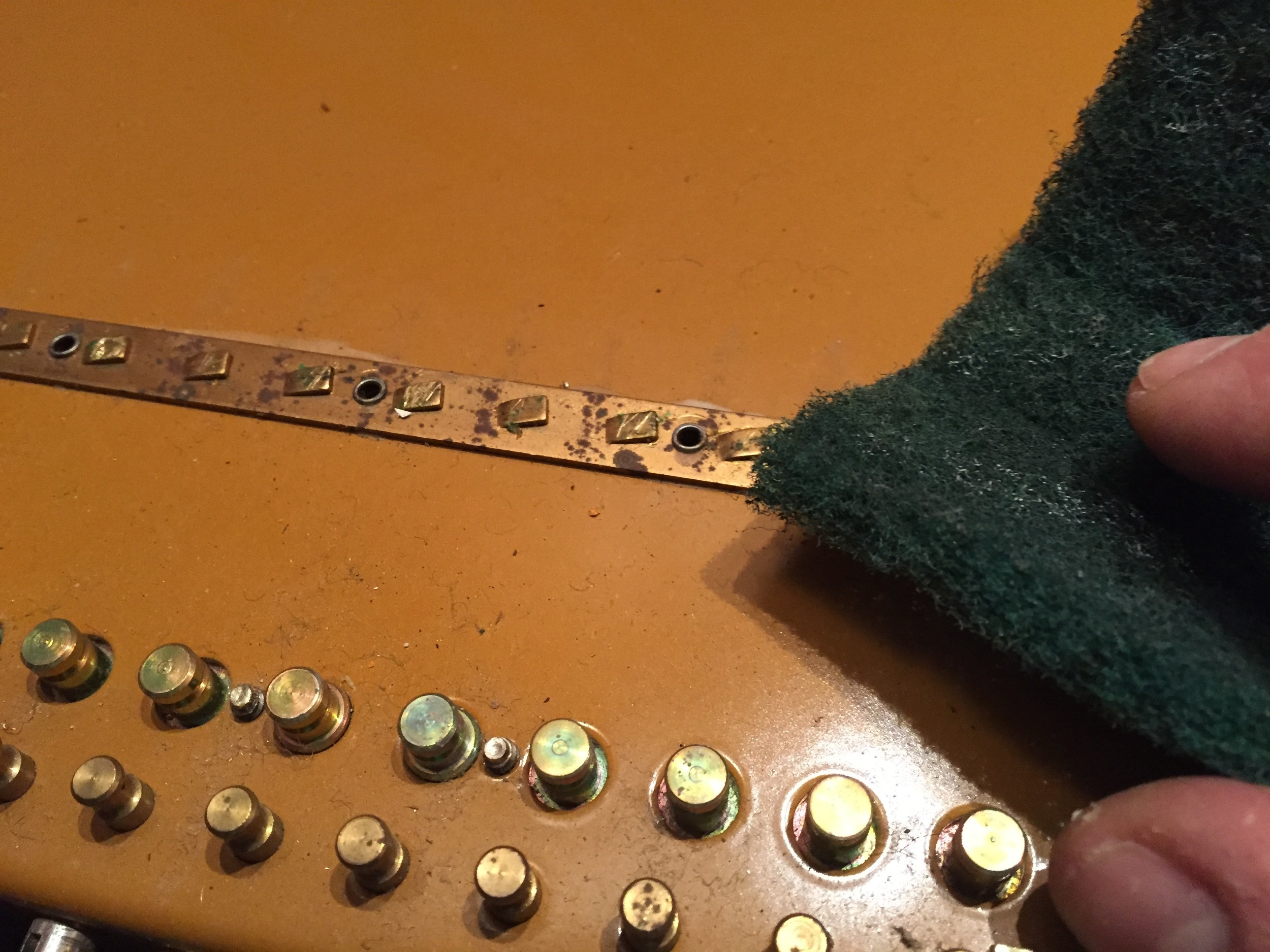 Removing corrosion with a Scotch-brite pad.