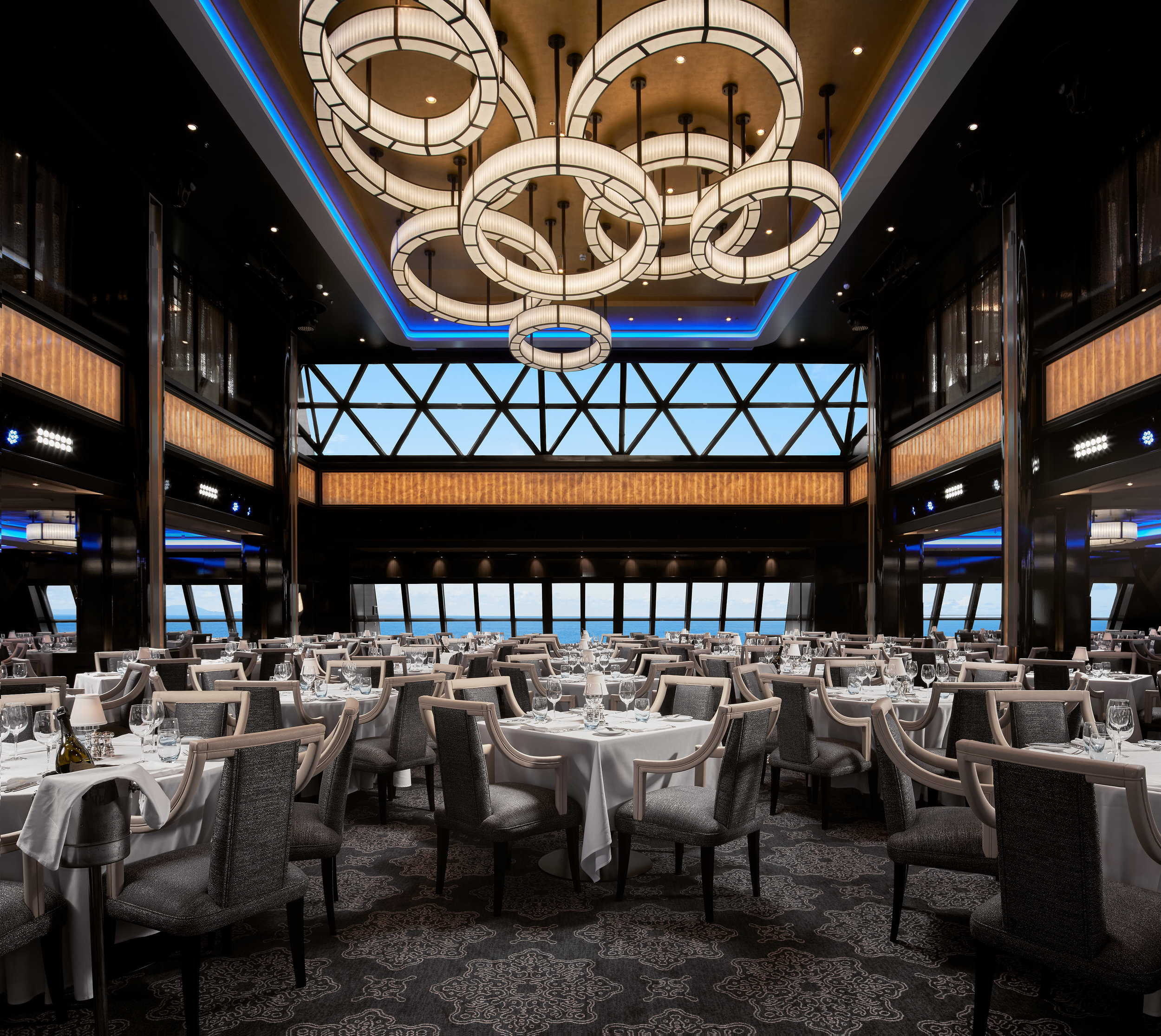 """The Manhattan Dining Room on the Norwegian Bliss. This was one of the larger files of the bunch as it required all of these tables to be lit individually, and stitching the light fixture from a different plate captured with my tilt-shift lens. The ship was also docked in port while we took this shot, so the """"view"""" had to be replaced with what it would look like if the ship were at sea."""
