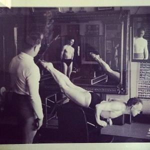 Joe Pilates teaching swan dive on the Wunda Chair in his original studio in NYC.