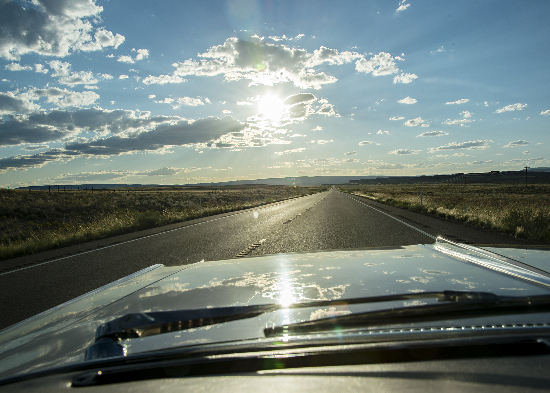 Heading into the sun, the clouds create a mirror image on the hood. Nikon D800, 24-120mm lens @ 30mm, iso 200, f11, 1/800 sec.