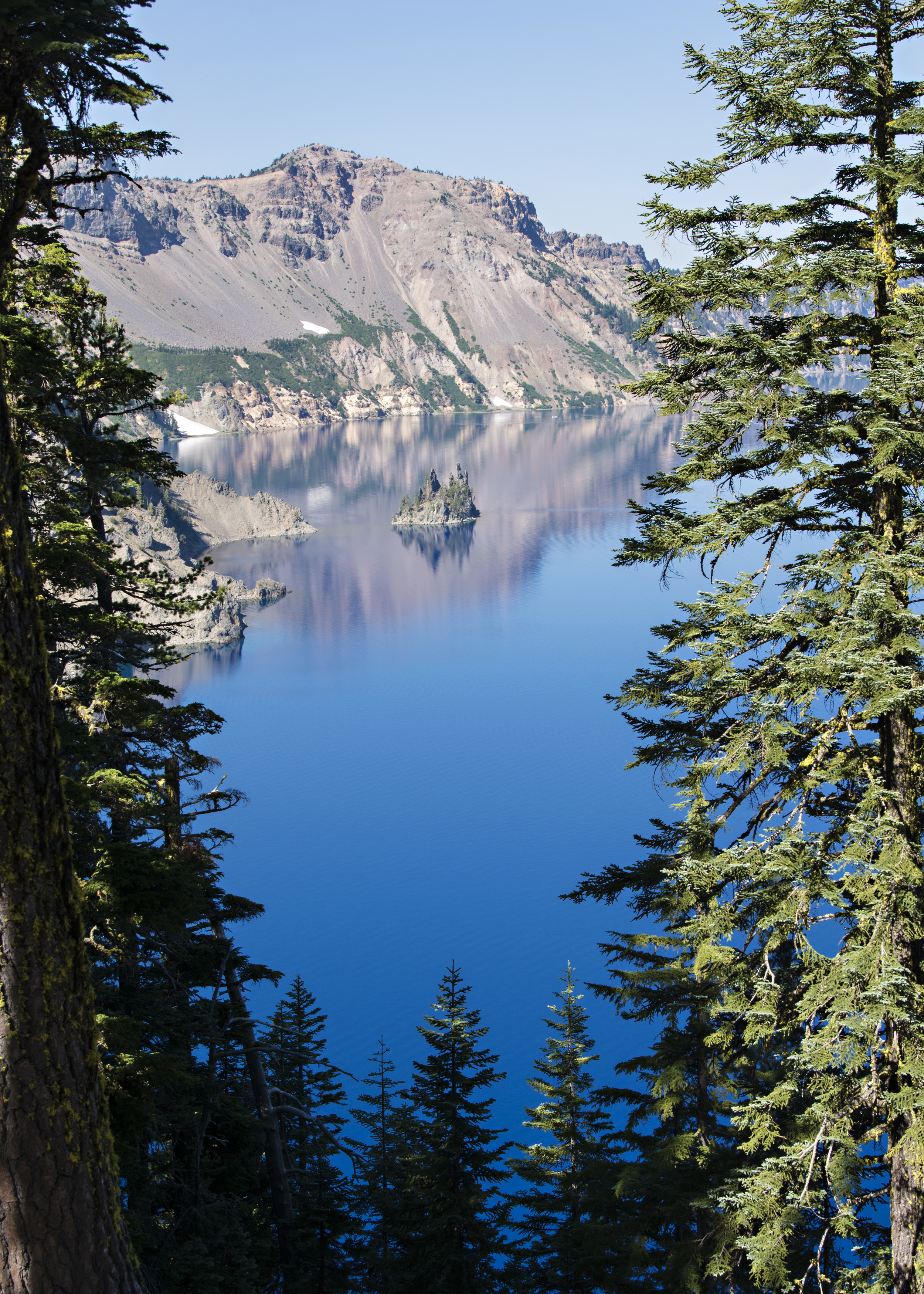 Crater Lake is impossibly blue. This is a view through the trees to Phantom Shiprock. Nikon D800, Nikkor 24-120mm @ 38mm,ISO 100, f8, 1/100 sec.