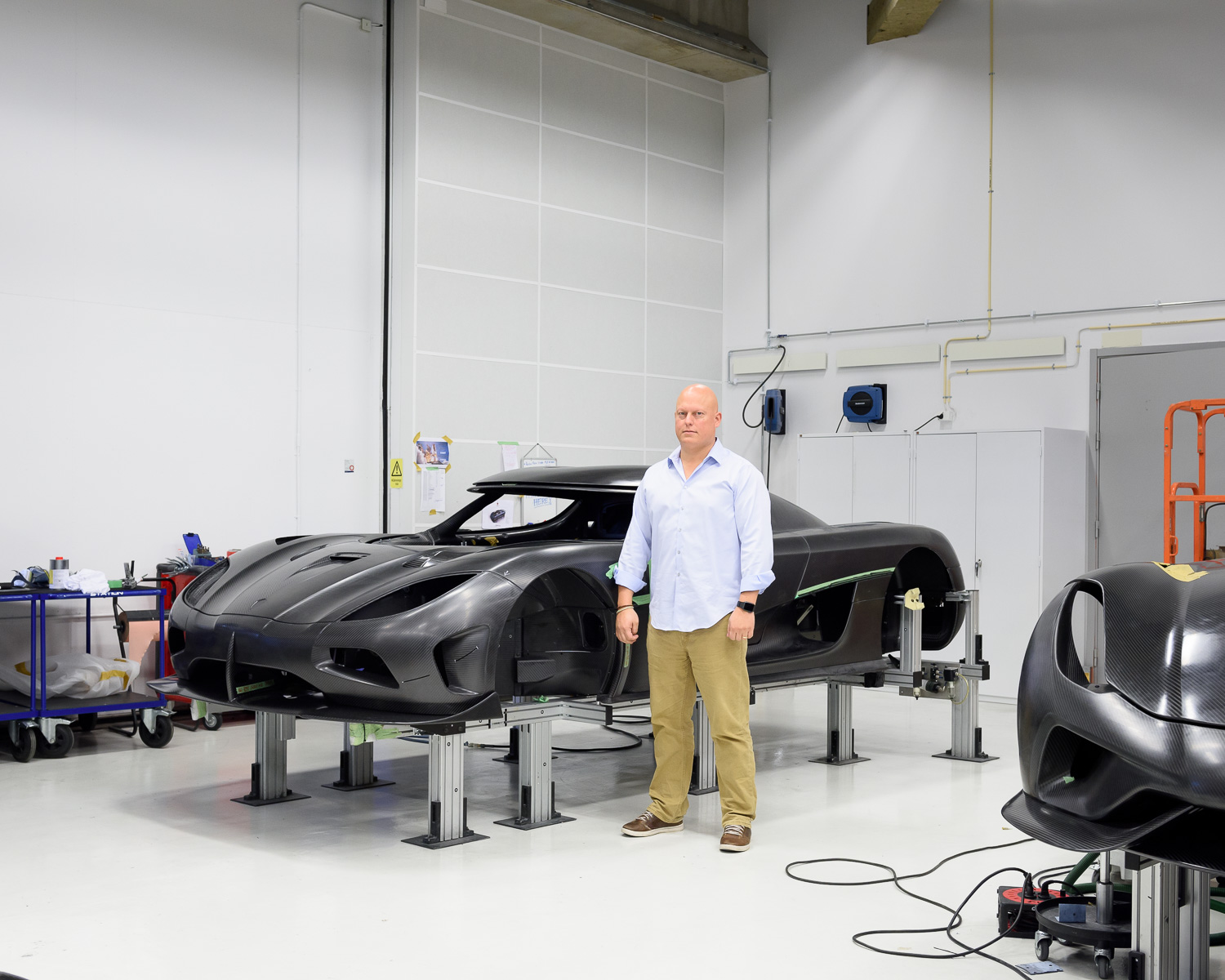 Christian von Koenigsegg standing in front of the shell of what will become one of the fastest cars in the world.