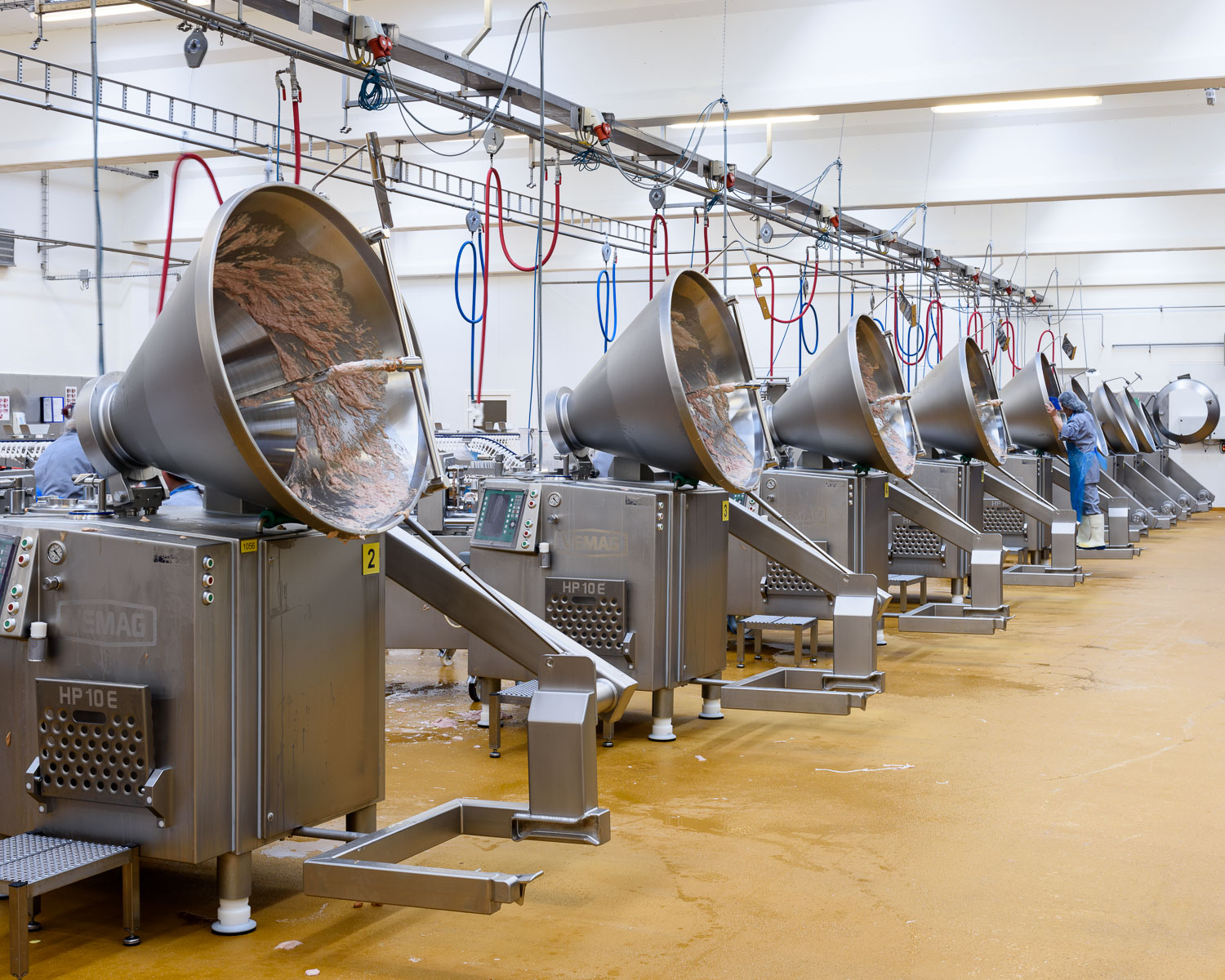Machines that feed sausage meat into the casings are bering cleaned.