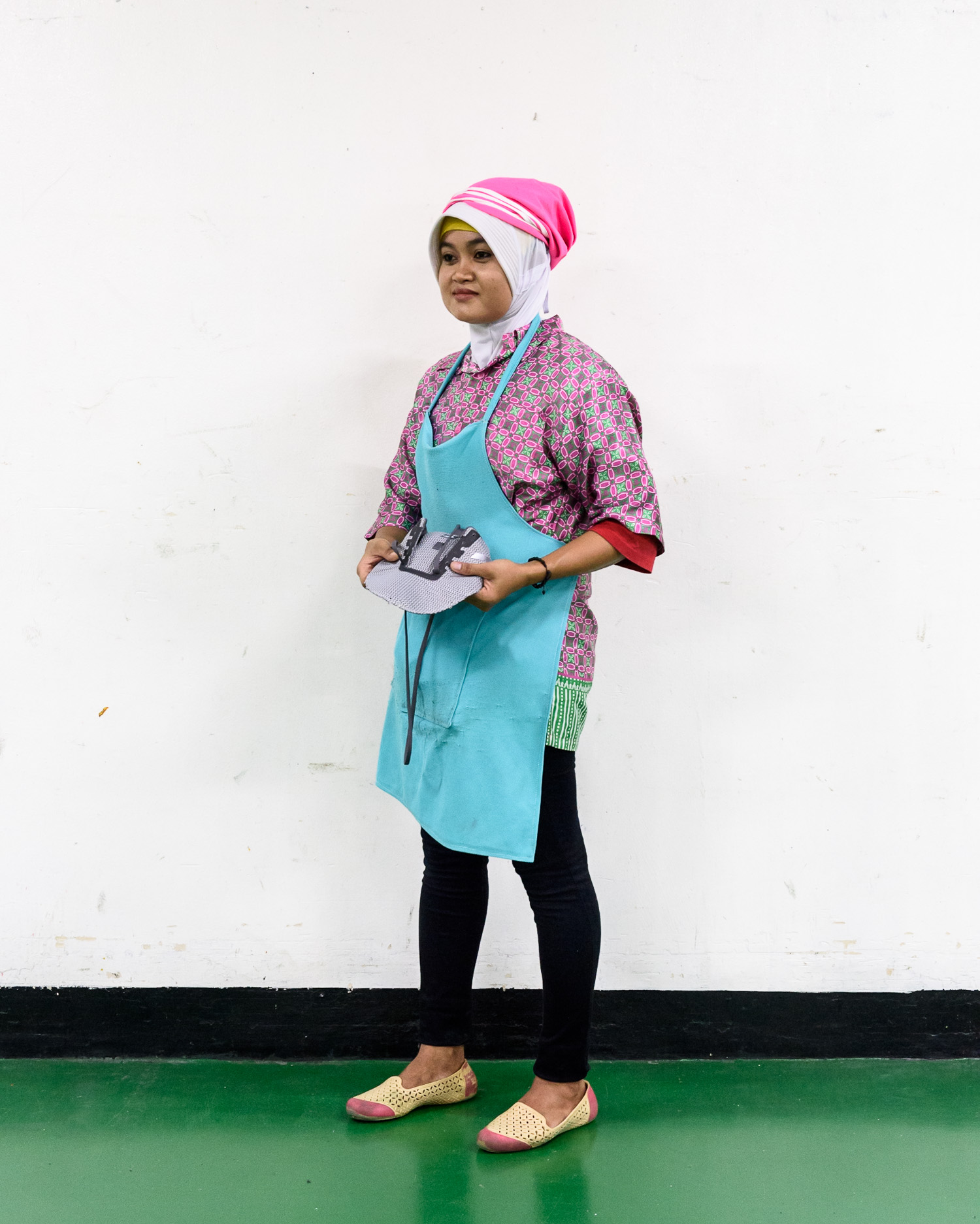 A worker at the PWI factory, which employs over 10,000 people. 75,000 pairs of shoes are produced every day, 22 million pairs per year