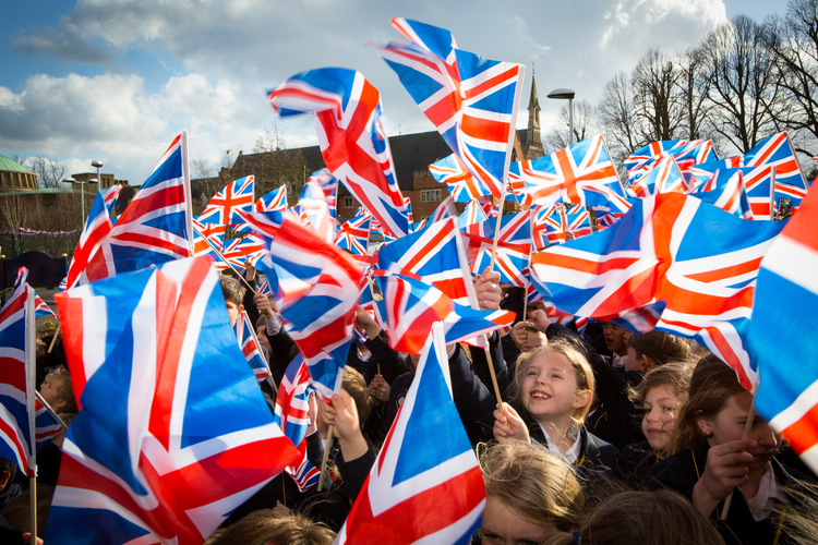 Children waving Union Jack flags for a PR Photography photo shoot