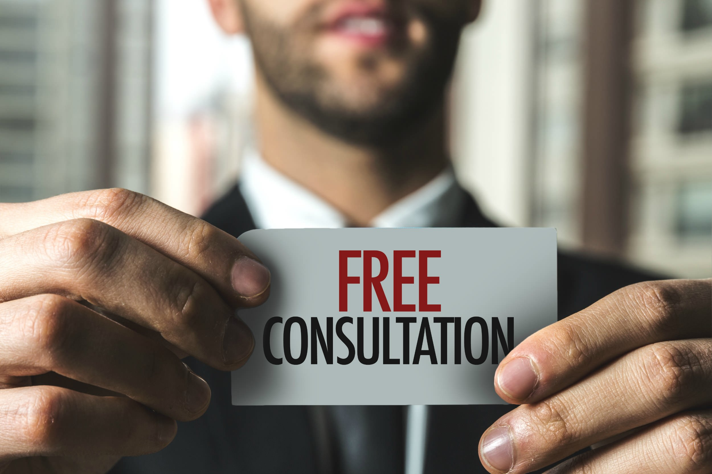 Man holding up a card that says free consultation