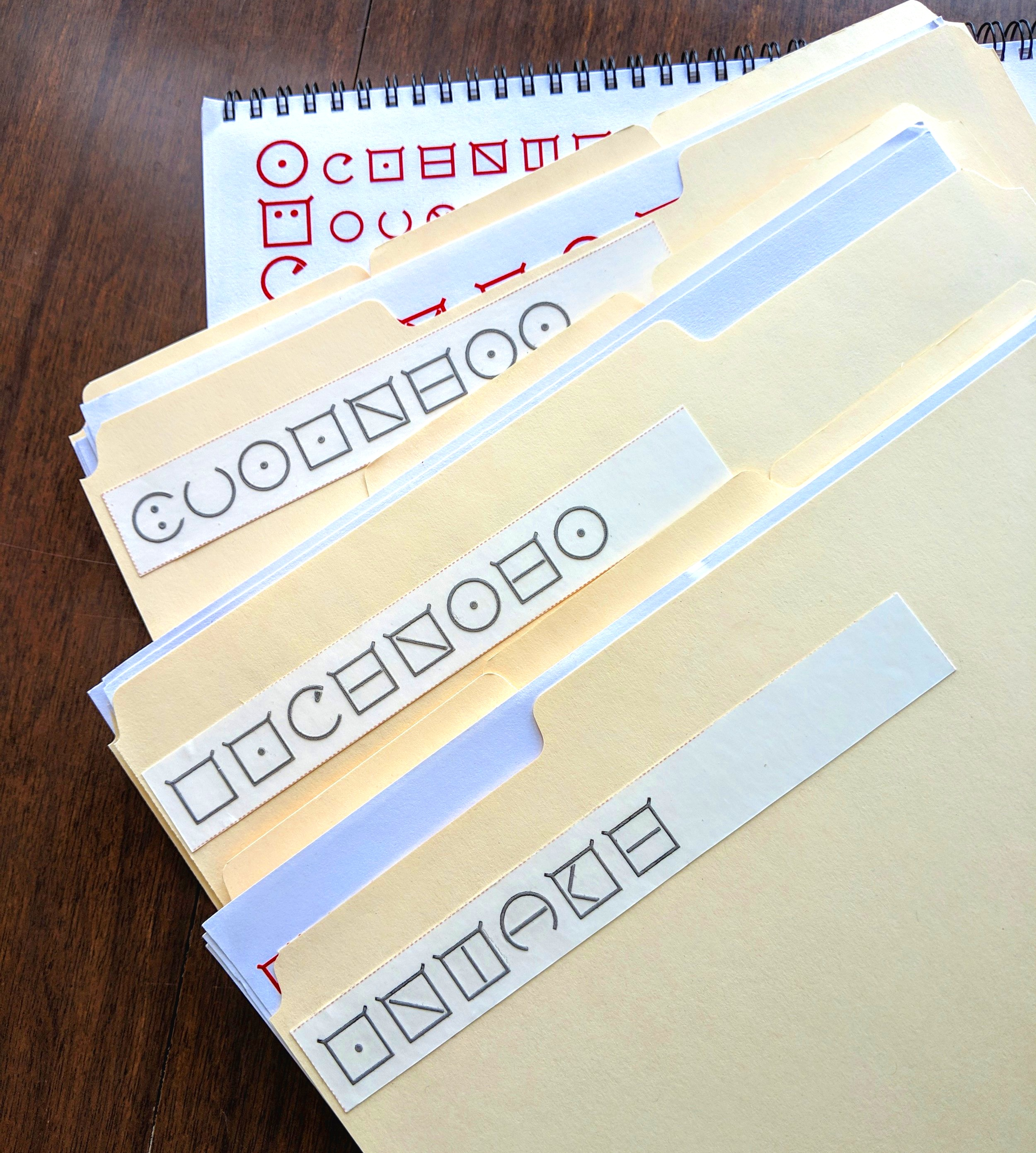 "Manila tab folders with adhesive ELIA Frame labels saying ""business"", ""licenses"", and ""intake""."