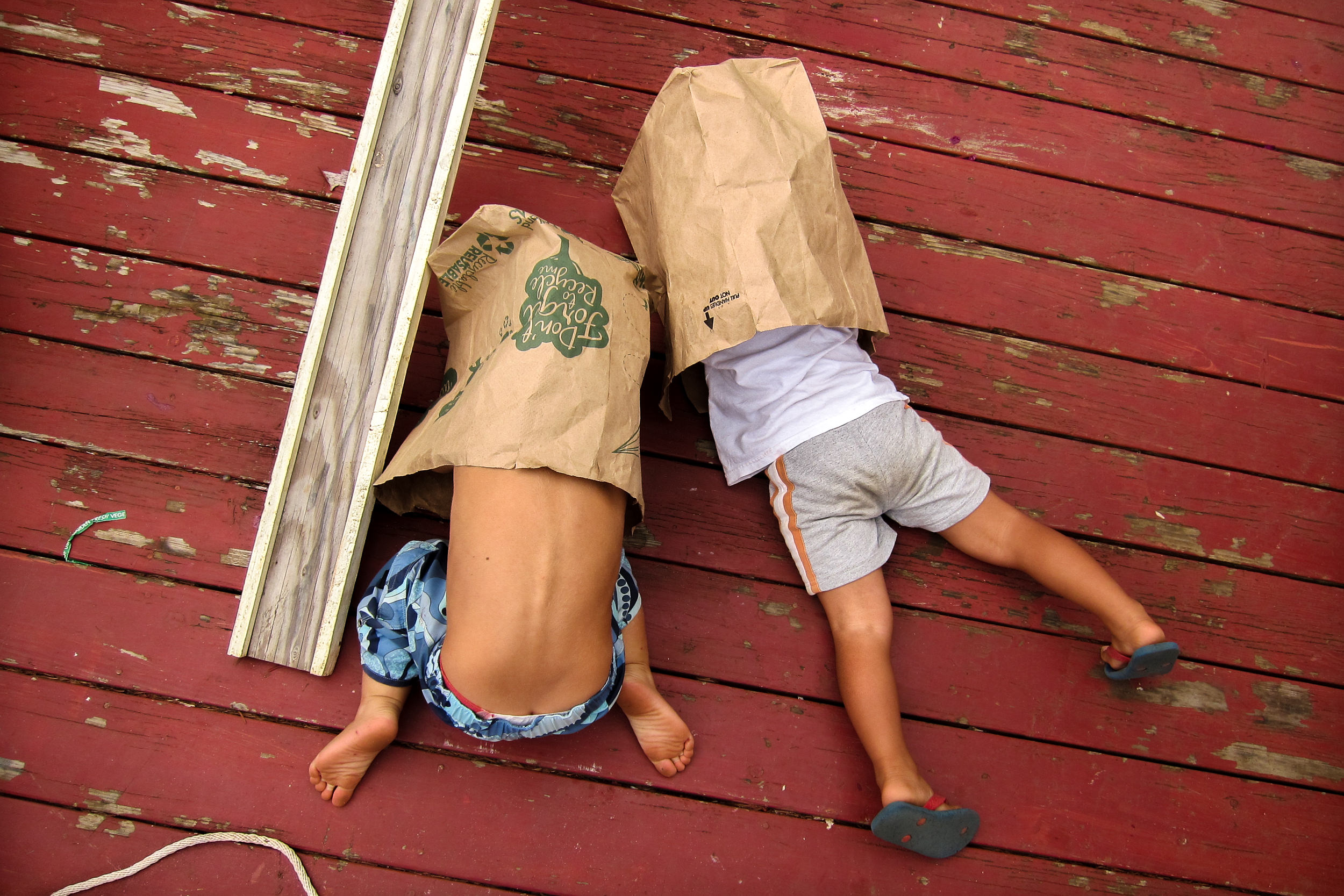 Molly Rees Photo - Documentary Childhood Photography - Overhead Portrait of two boys in paper bags by M. Menschel