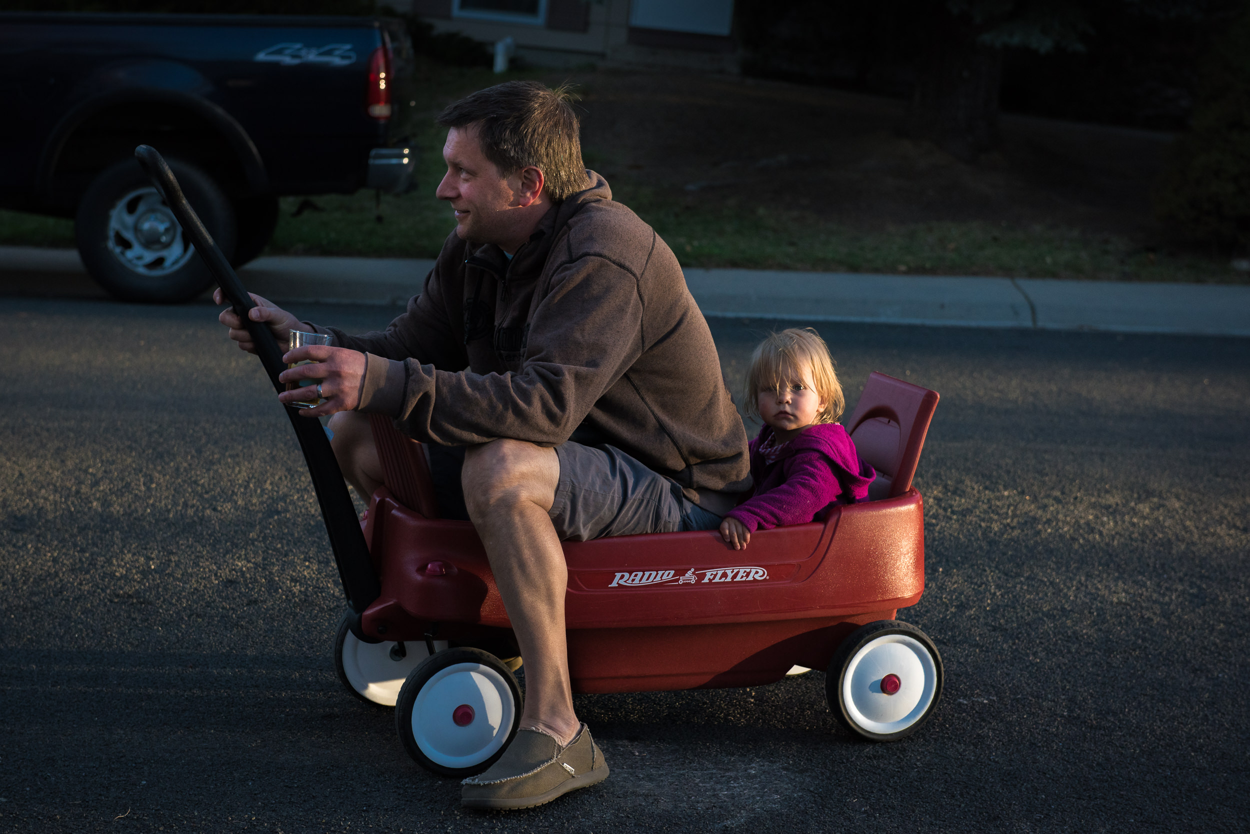 Documentary Family Photography in Denver, Colorado - dad sitting in red wagon with girl