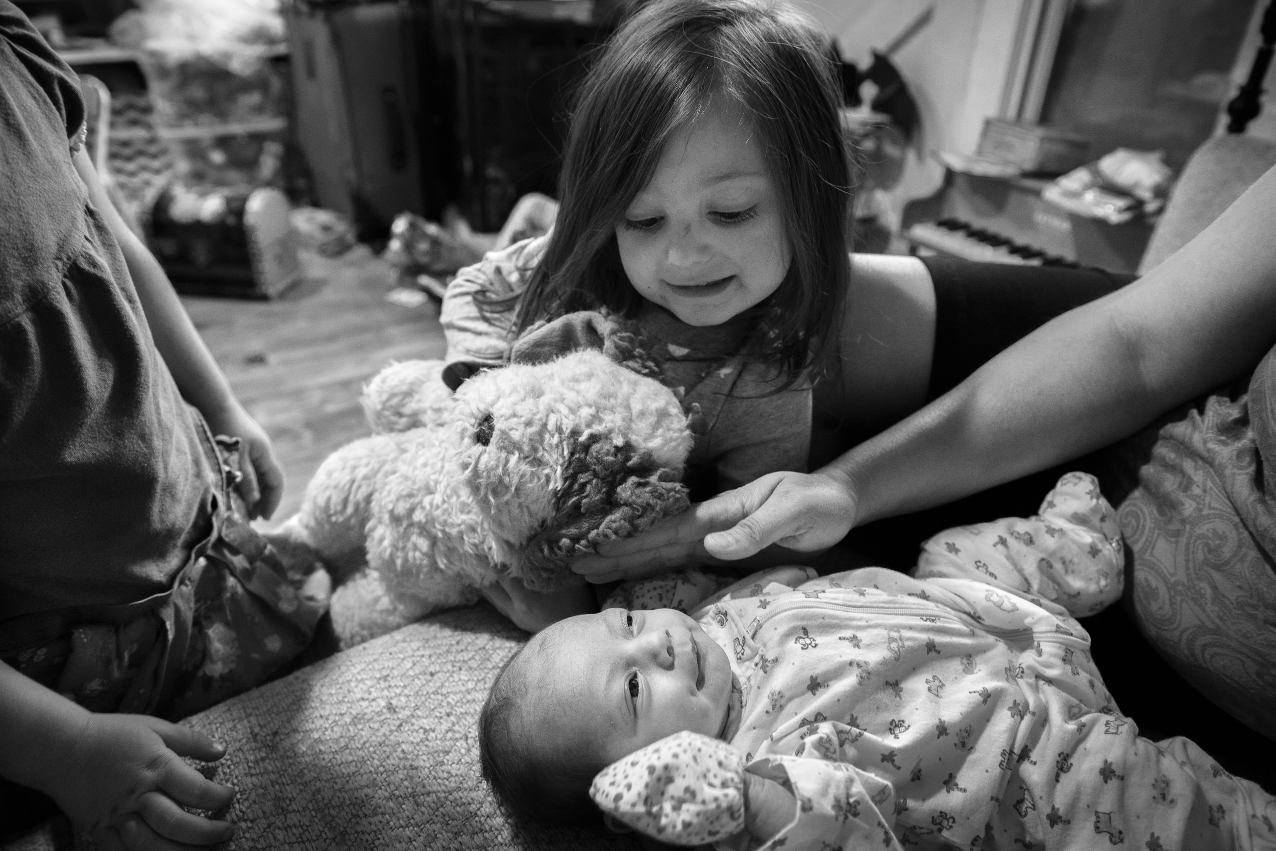 Black and White Documentary Newborn Photography in Denver, Colorado - sister looking at baby