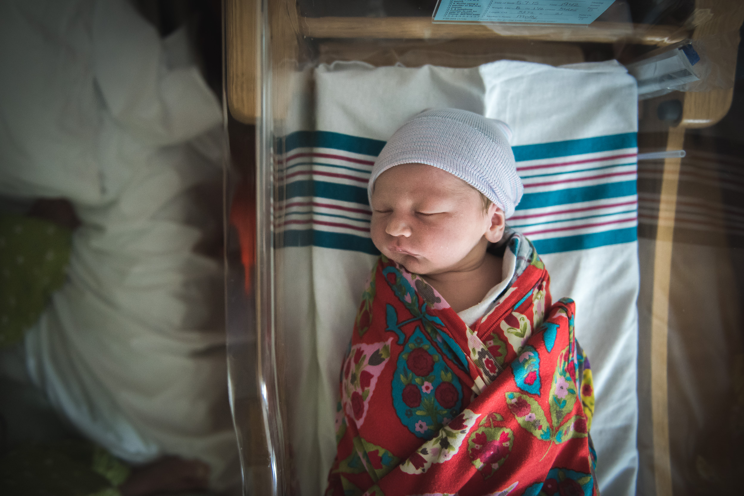Molly Rees Photo - Documentary Newborn Photography in Denver, Colorado - overhead portrait of baby in hospital bassinet by M. Menschel