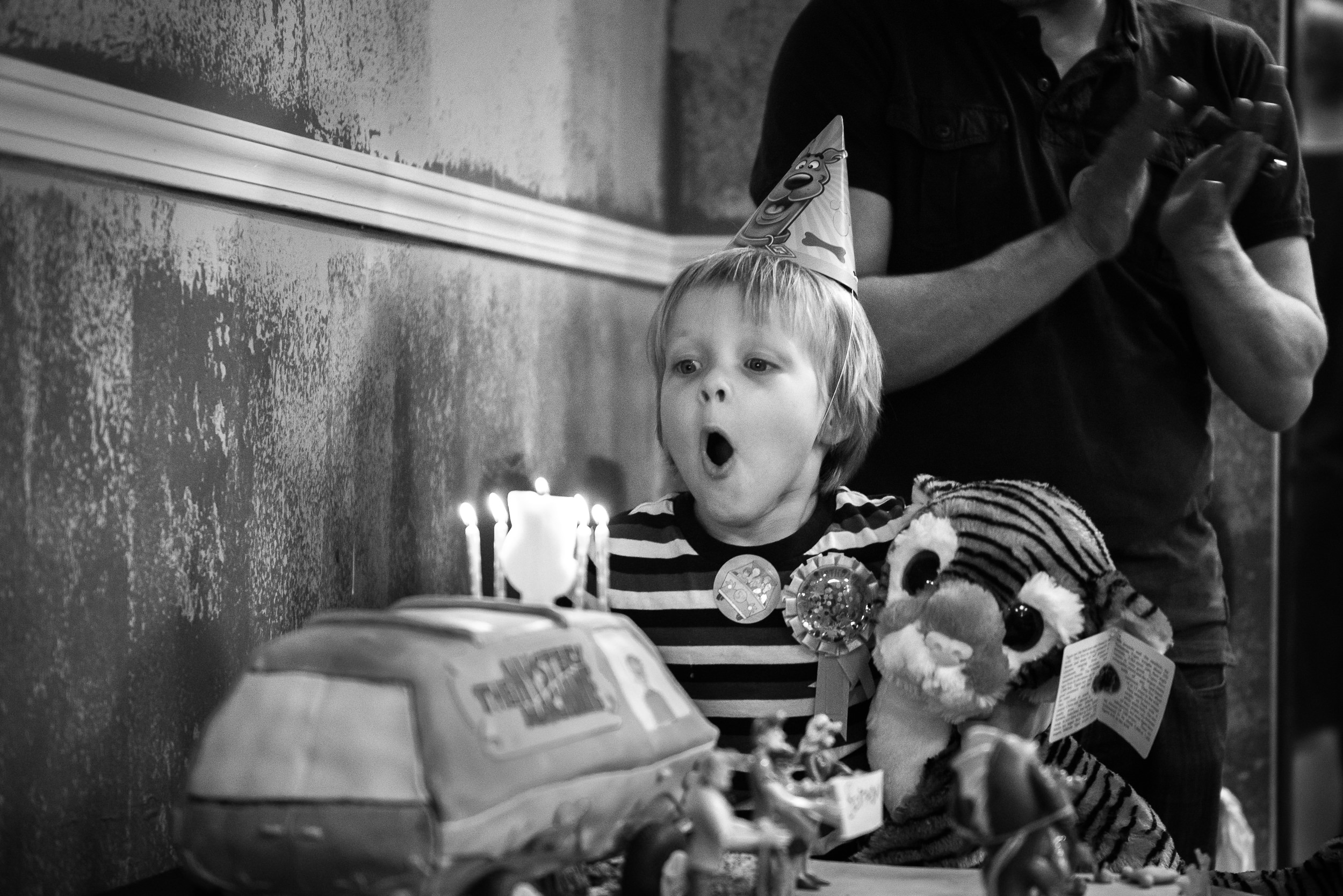 Black and White Documentary Family Photography in Denver, Colorado - birthday boy blowing out candles on cake at party