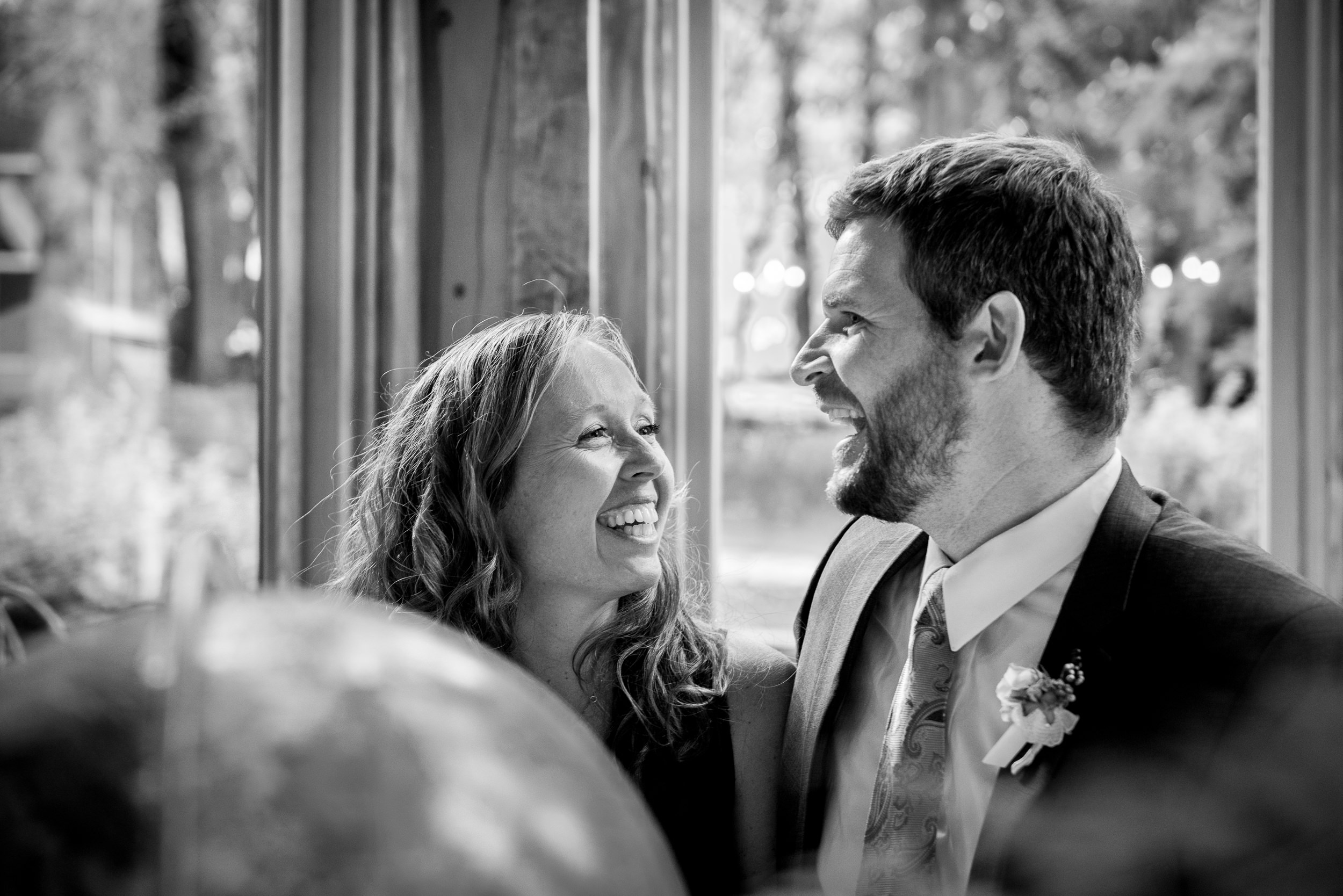 Black and White Documentary Wedding Photography in Denver, Colorado - couple laughing at reception dinner