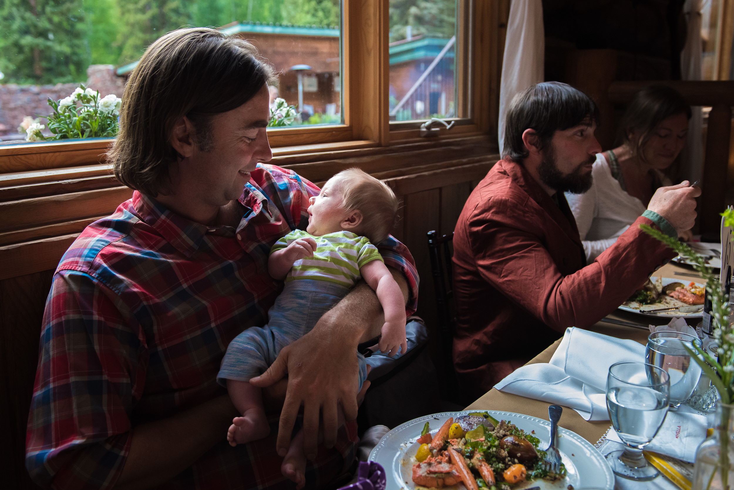 Documentary Family Photography in Denver, Colorado - father with baby at wedding reception dinner