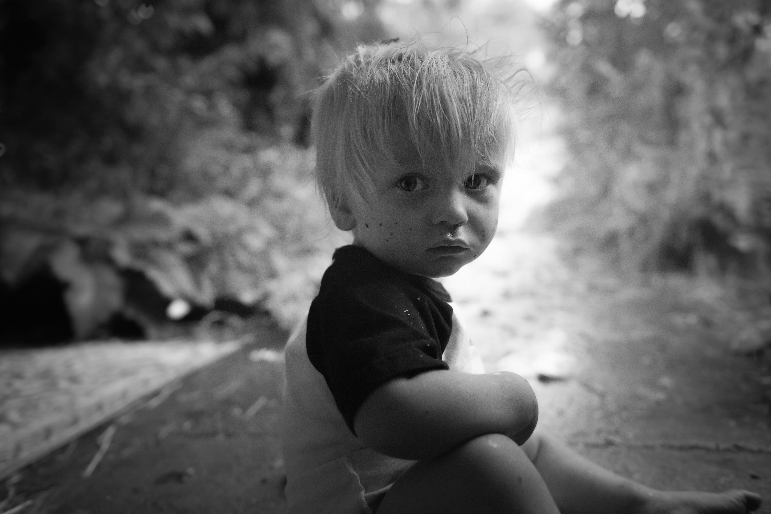 Blog - The Pen & Camera - Gratitude Journal, Inspirational, Writing - Molly Rees Photo - Black and White Documentary Childhood Photography - portrait of young boy outside in rain by M. Menschel
