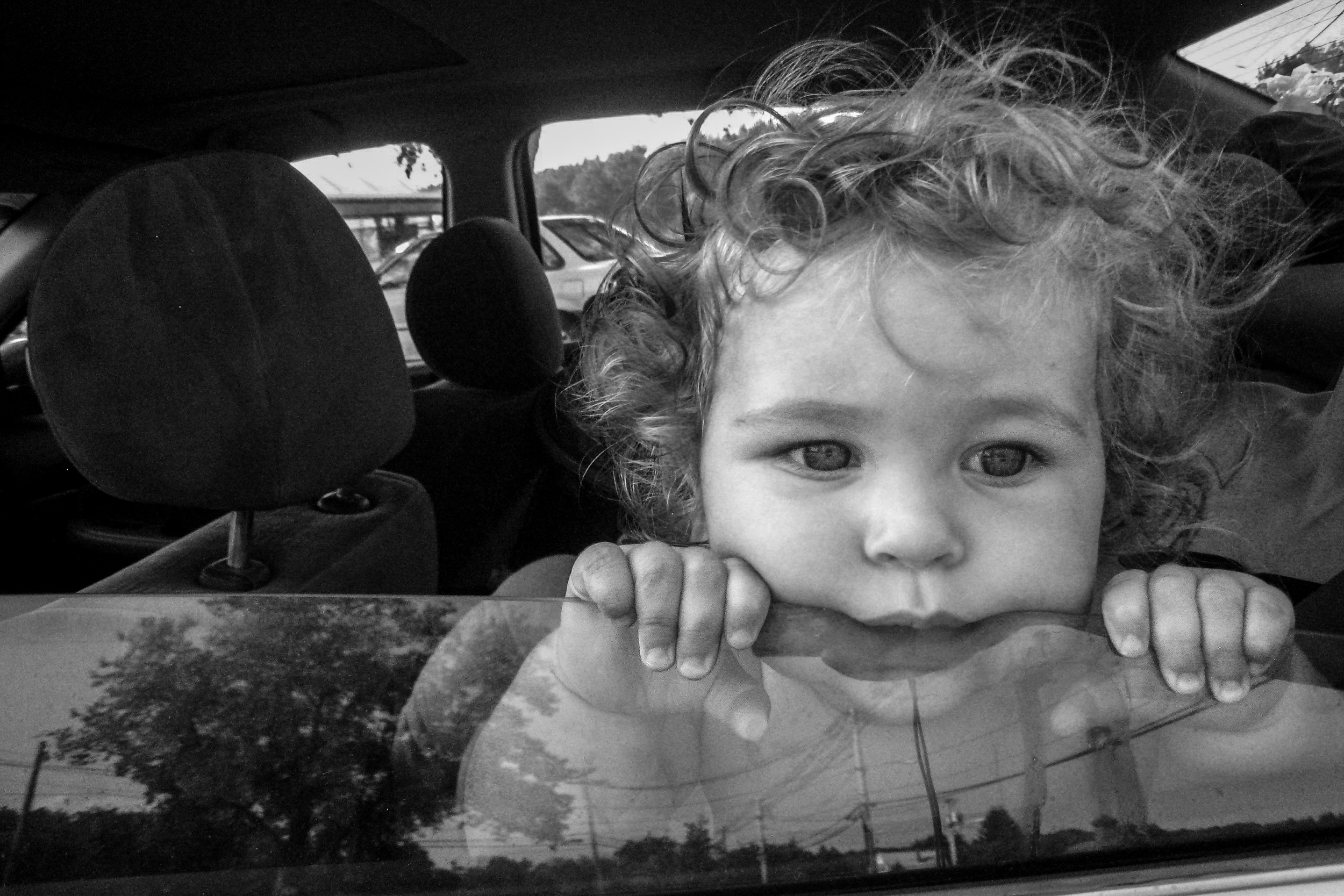 Molly Rees Photo - Black and White Documentary Childhood Photography - Portrait of toddler boy looking out car window by M. Menschel