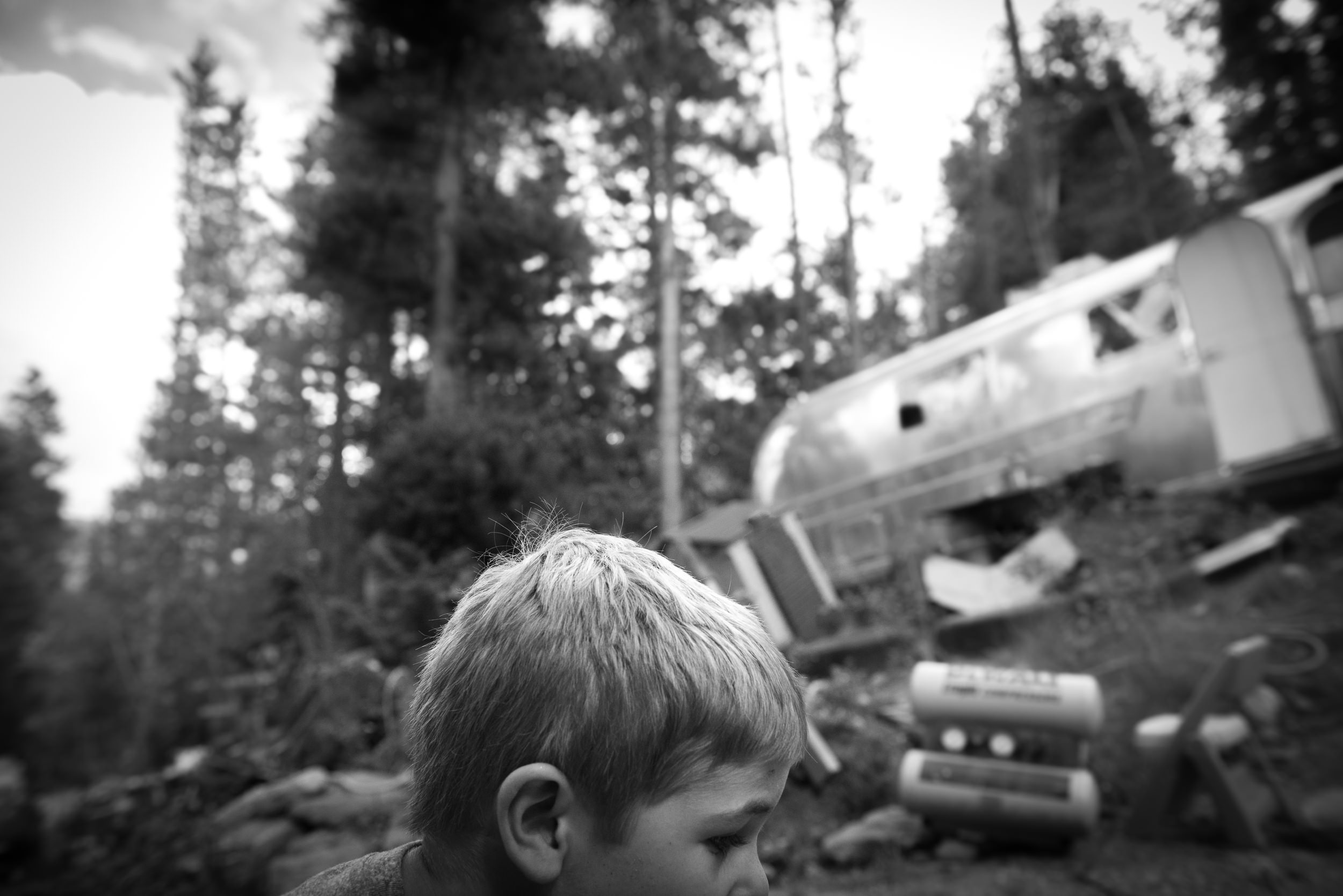 "Inspirational Poetry Blog - The Pen & Camera - Rumi quote ""Let yourself"" - Molly Rees Photo - Black and White Documentary Childhood Photography - Portrait of a Boy outdoors with airstream trailer in Evergreen Colorado by M. Menschel"