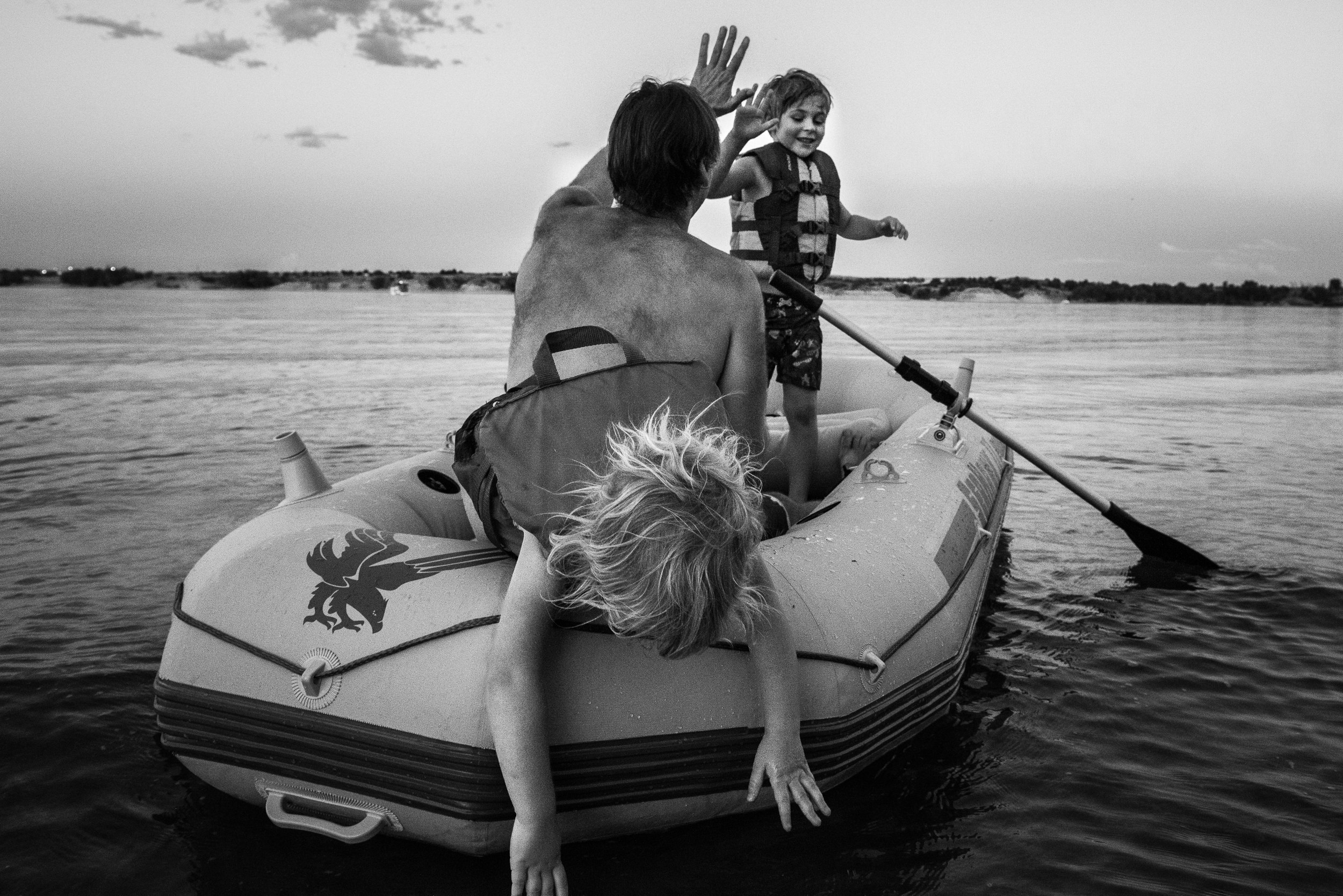 Blog - The Pen & Camera - Molly Rees Photo - Black and White Documentary Childhood Photography - children in raft giving high-five at Chatfield Reservoir in Denver, Colorado by M. Menschel