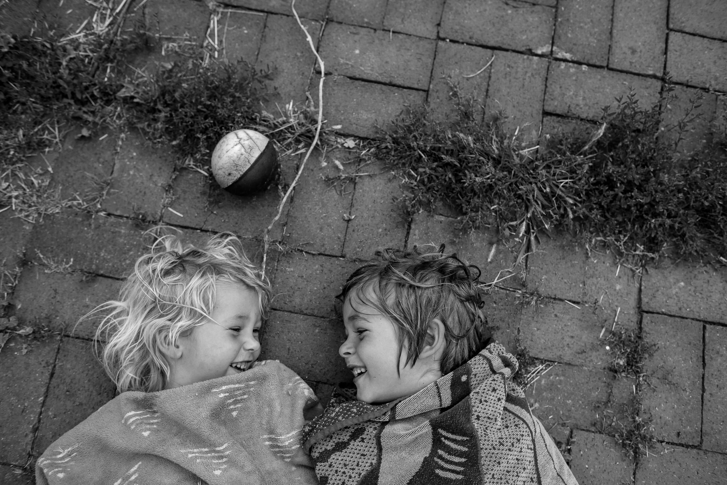 Molly Rees Photo - Black and White Documentary Childhood Photography - Overhead siblings portrait of children laughing by M. Menschel