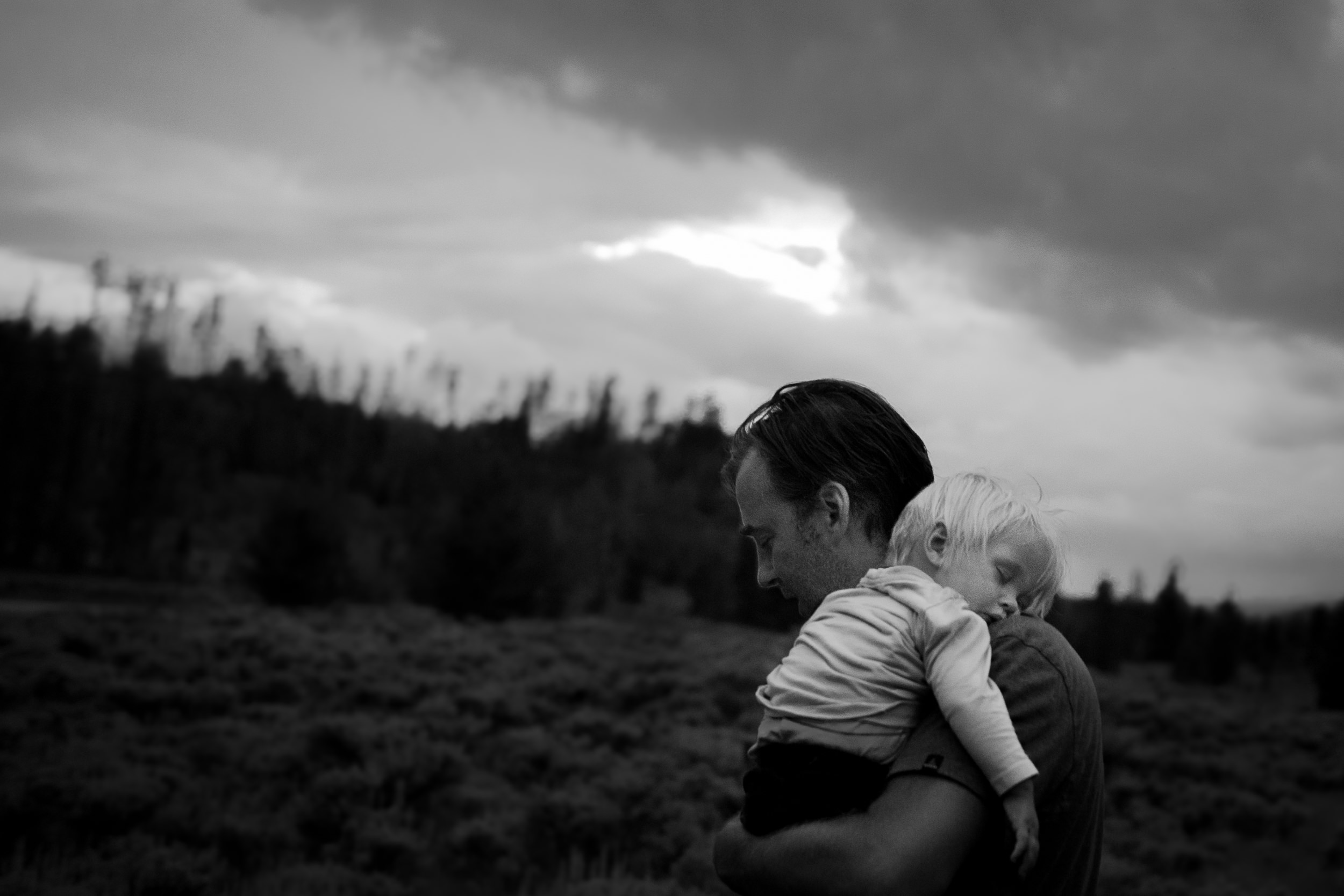Writing Blog - The Pen & Camera - Molly Rees Photo - Black and White Documentary Childhood Photography - night time portrait of baby boy asleep on fathers shoulder in Grand Lake Colorado by M. Menschel