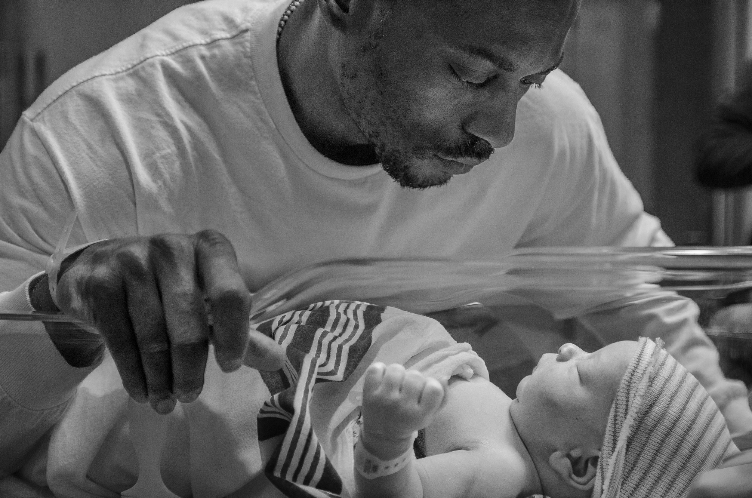 Molly Rees Photo - Black and White Documentary Newborn Photography in Denver, Colorado - father looking at baby in hospital bassinet by M. Menschel