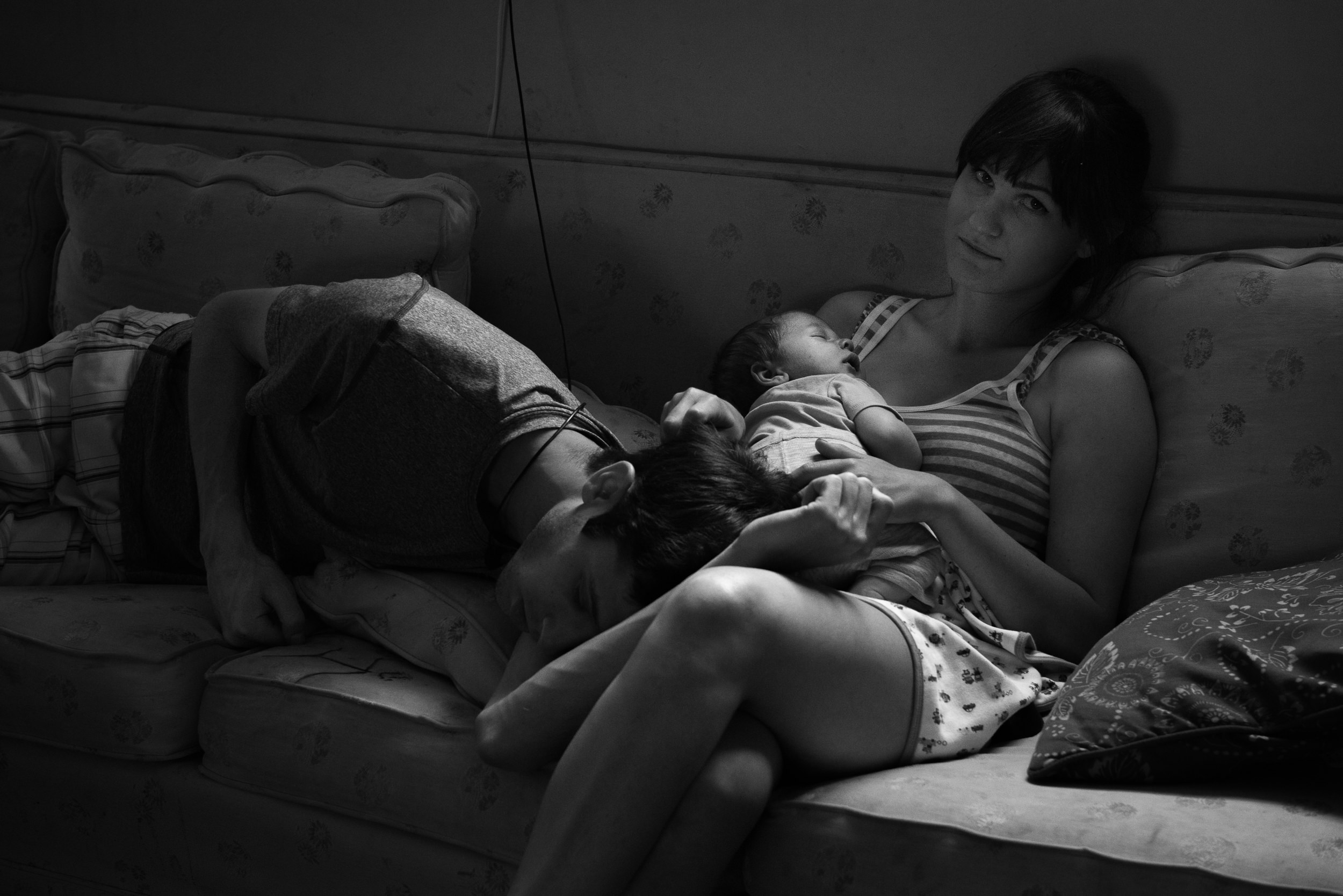 Molly Rees Photo - Black and White Documentary Family Photography - Portrait of tired new parents with newborn baby by M. Menschel