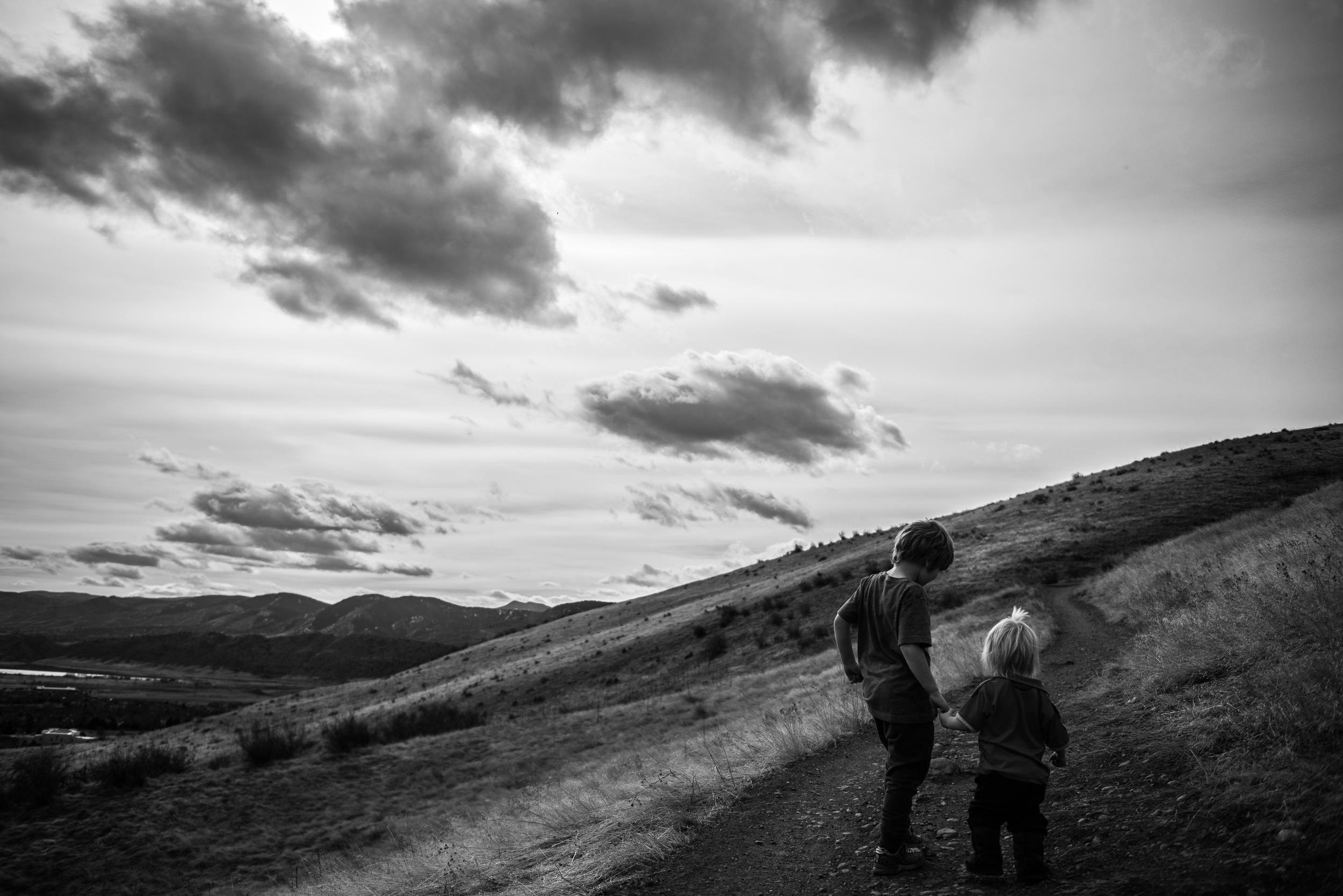 Blog - Molly Rees Photo - Black and White Documentary Childhood Photography - children holding hands on green mountain hiking trail in denver colorado by M. Menschel