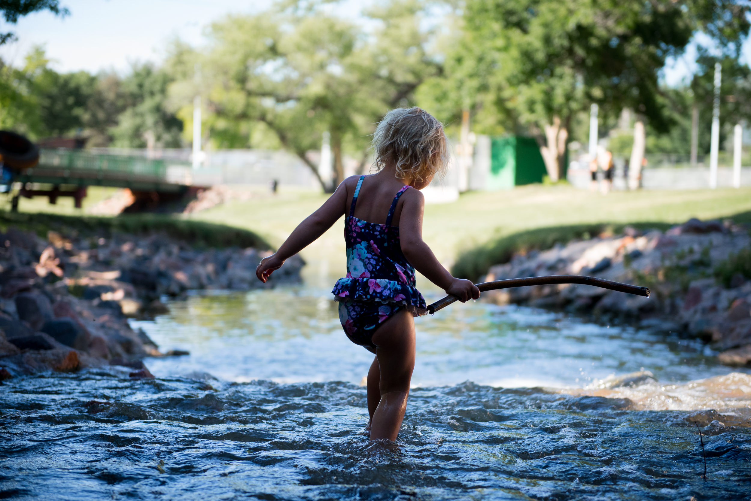 Blog - The Pen & Camera - Molly Rees Photo - Documentary Childhood Photography - girl wading in stream at Belleview Park in Denver, Colorado by M. Menschel