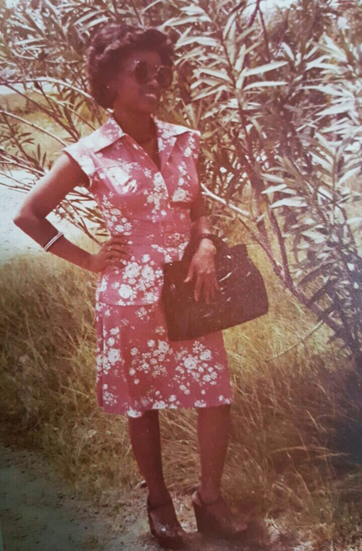 Mom with a backdrop of plants back home in Guyana