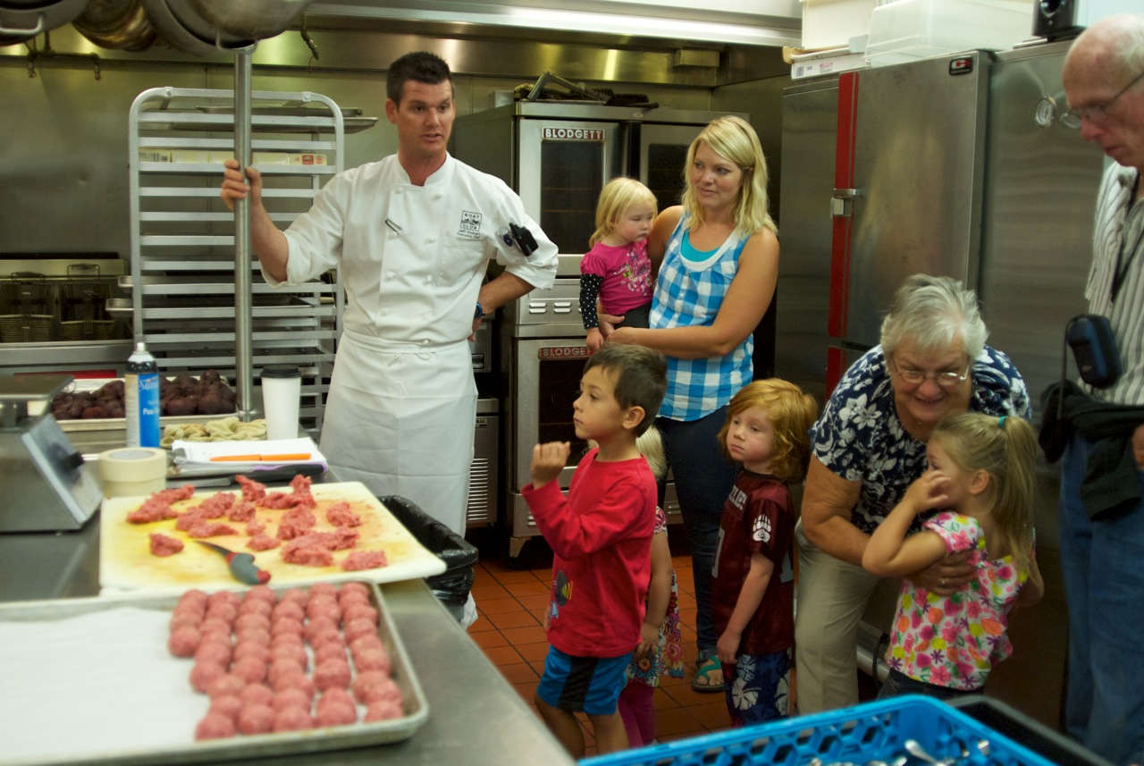 Chef Jeff Hobart giving the students a tour of the kitchen at the Whitefish Lake Lodge. The elk meatballs that were served for the appetizer course can be seen in the foreground.