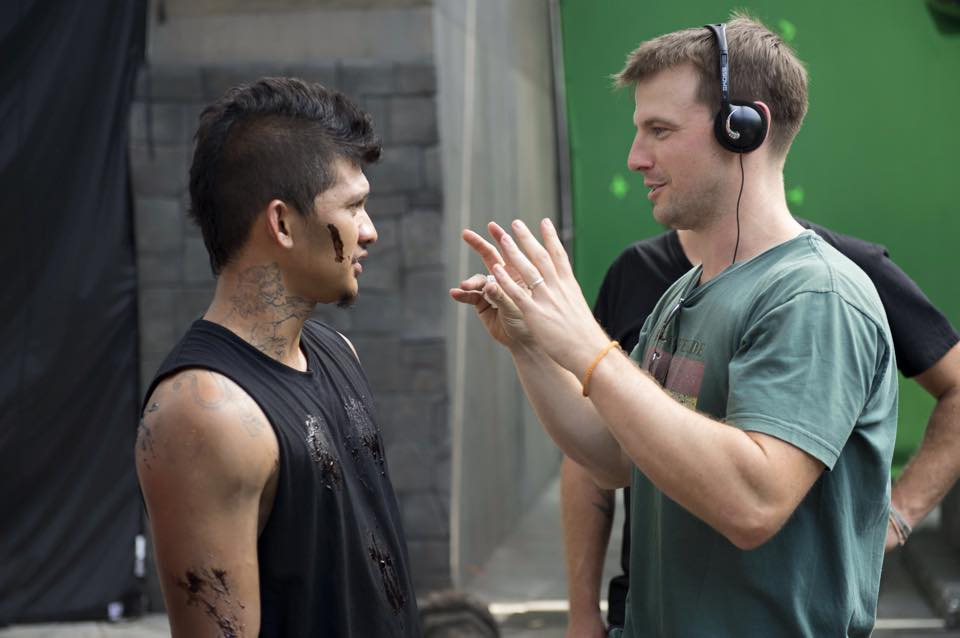 """Director Liam O'Donnell (right) on the set of 2017's """"Beyond Skyline"""" trying to describe what a dog named Crom looks like."""