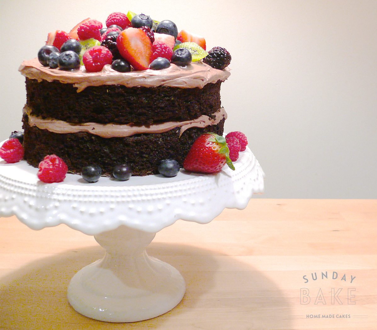 Moist chocolate cake with buttercream chocolate filling, topped with fresh berries