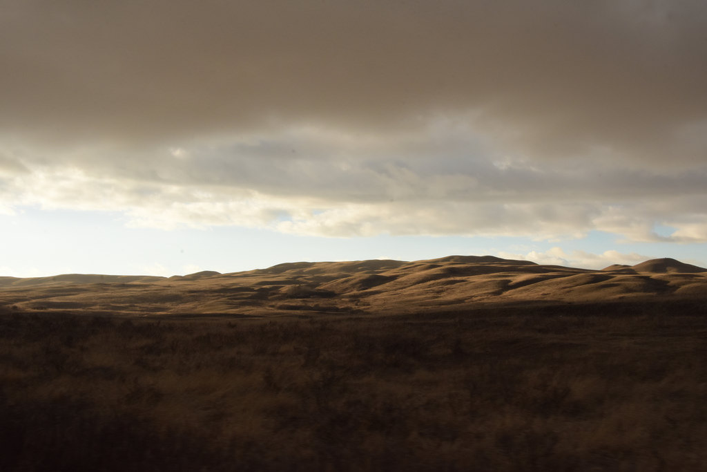 Low-hanging clouds and rolling grasslands.