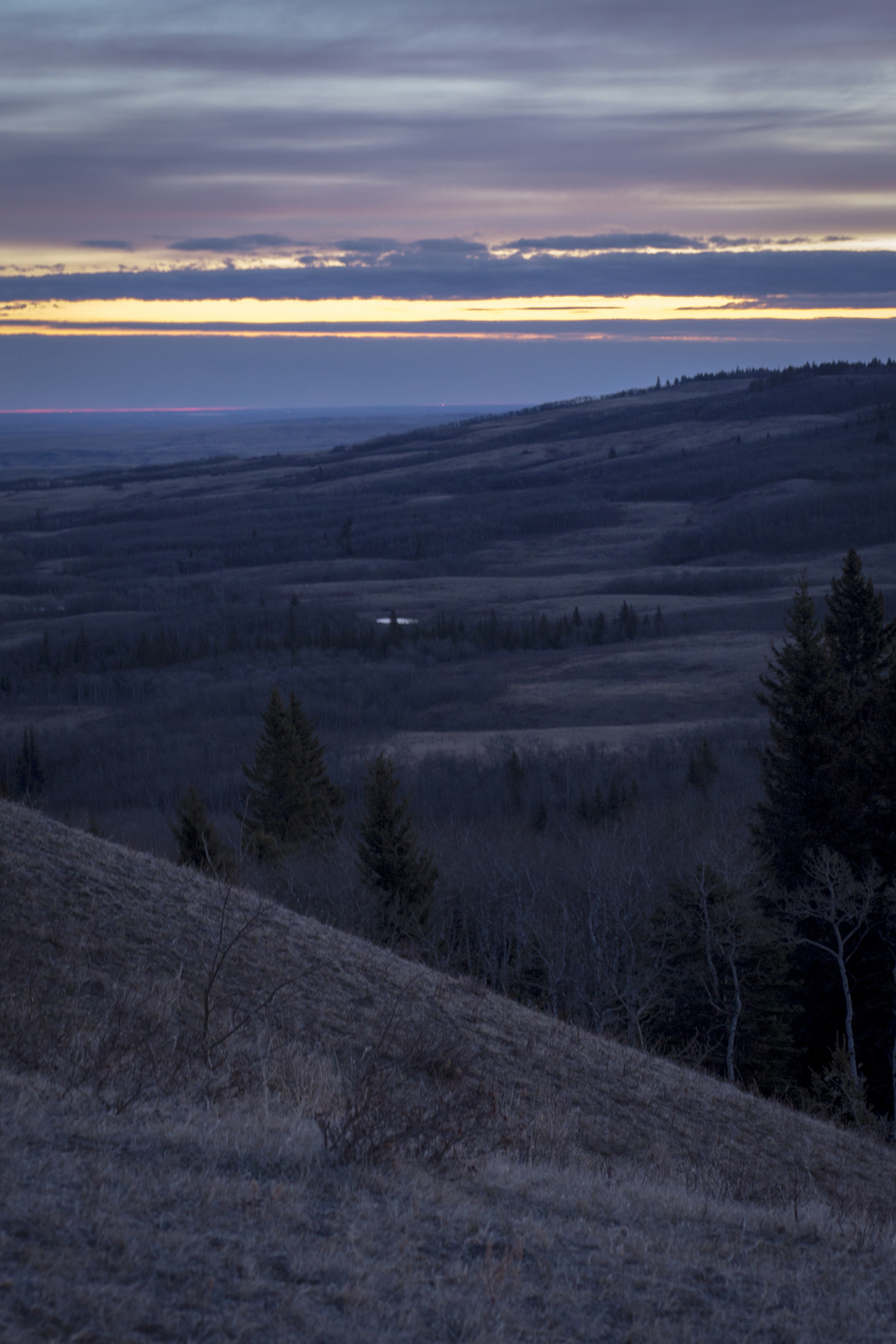 Hiking to Bald Butte - watching the sun rise behind a wall of cloud over the town of Maple Creek and Cypress Hills Interprovincial Park.