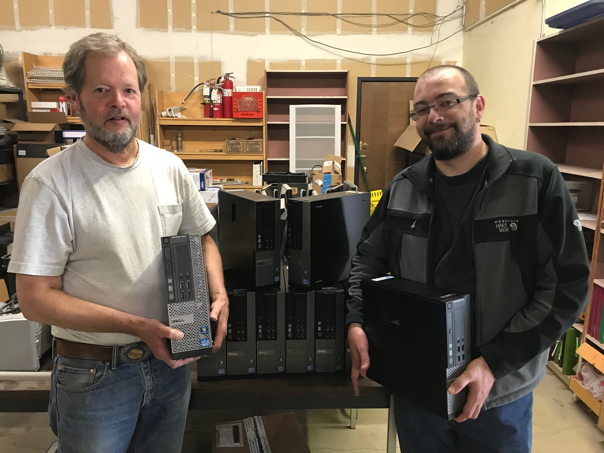 IT Director Jim Carpenter and IT Assistant Loren Tussing show of some of the donated PC towers provided to Looking Glass from SELCO, stored for cleaning and setup at the Looking Glass warehouse.