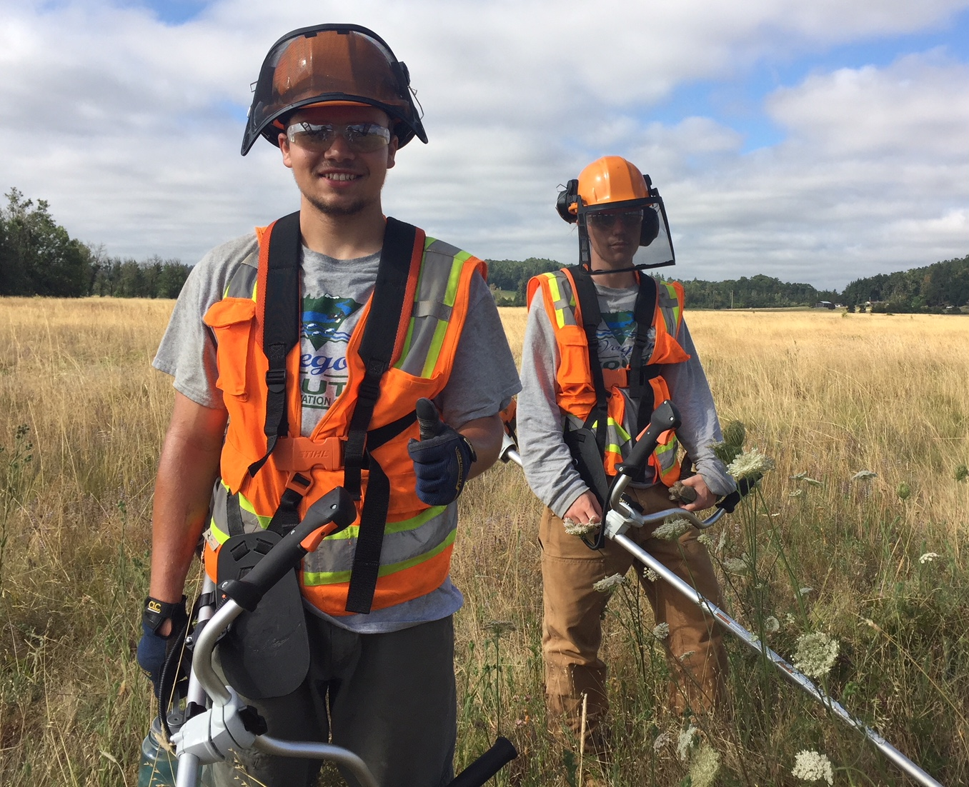2 members of Looking Glass' Lane Metro Youth Corps summer work crew show off their brush cutters as they trim invasive species from fields in West Eugene.