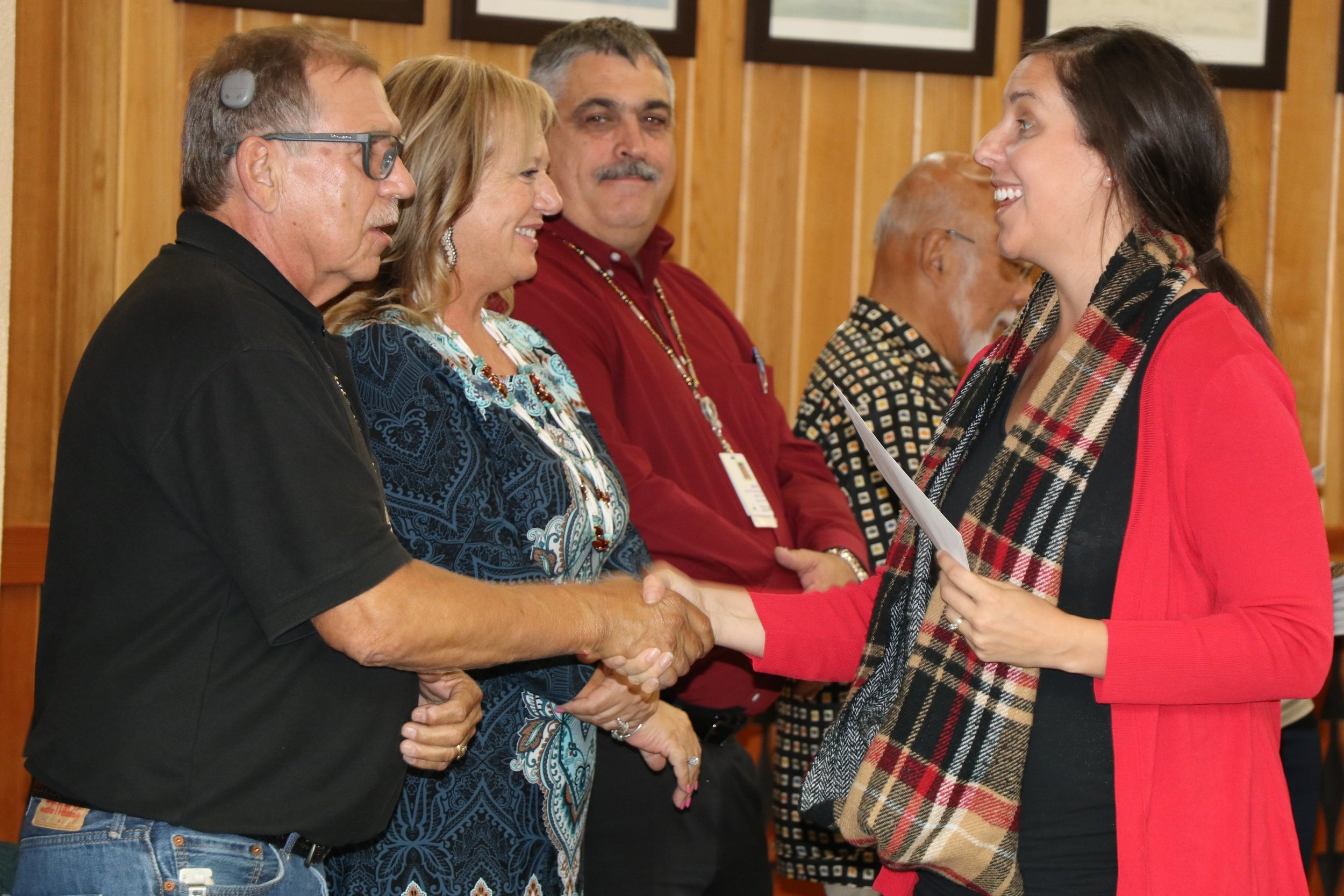 Becca Marx, grant writer for Looking Glass, accepts award and shakes hands with Spirit Mountain Community Fund Trustees (left to right) Jack Giffen, Jr, Denise Harvey, Ron Reibach, and Sho Dozono.