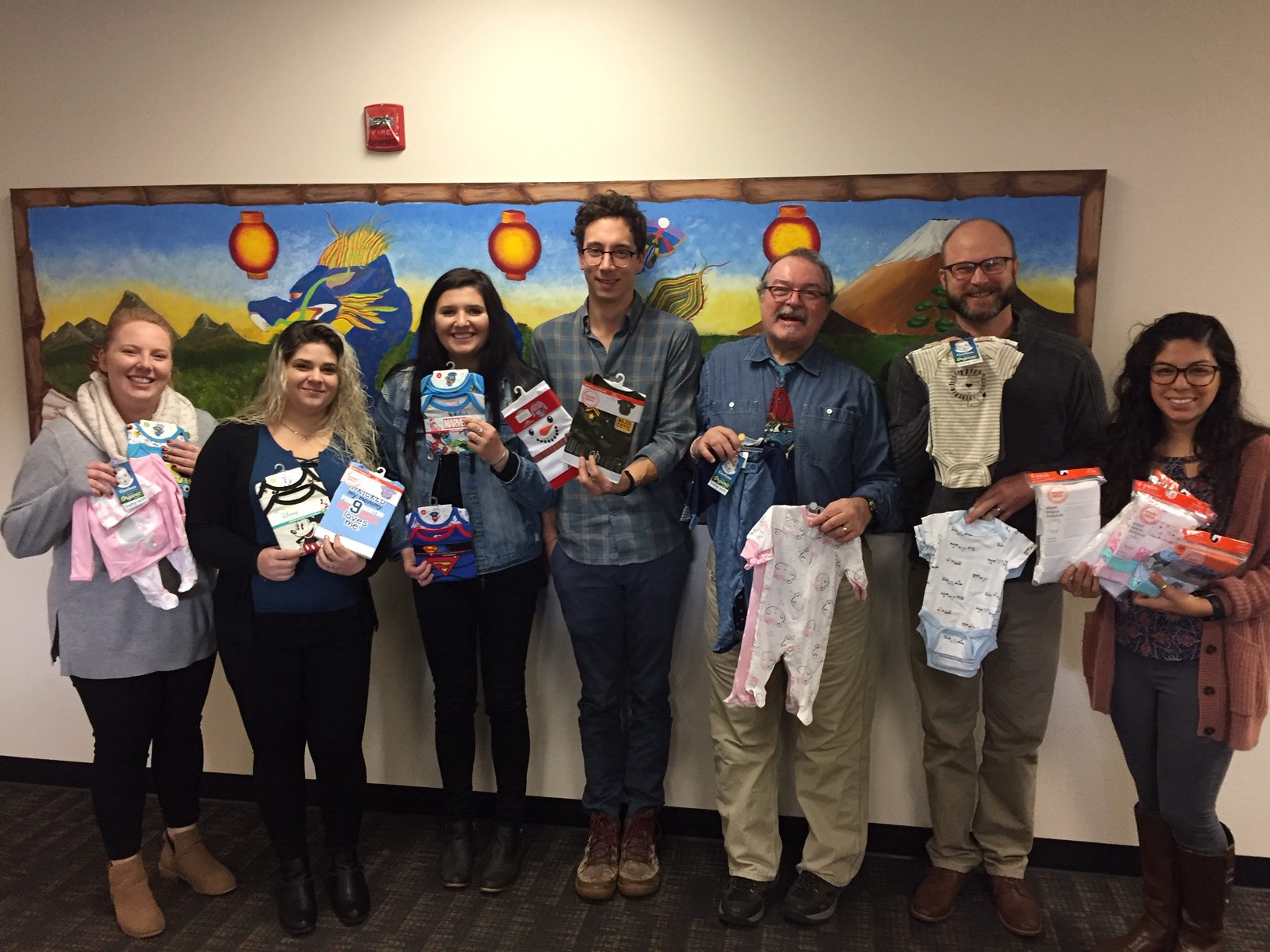 Riverfront School and Career Center staff show off a handful of the newborn baby clothes purchased with funding support from OCCU.
