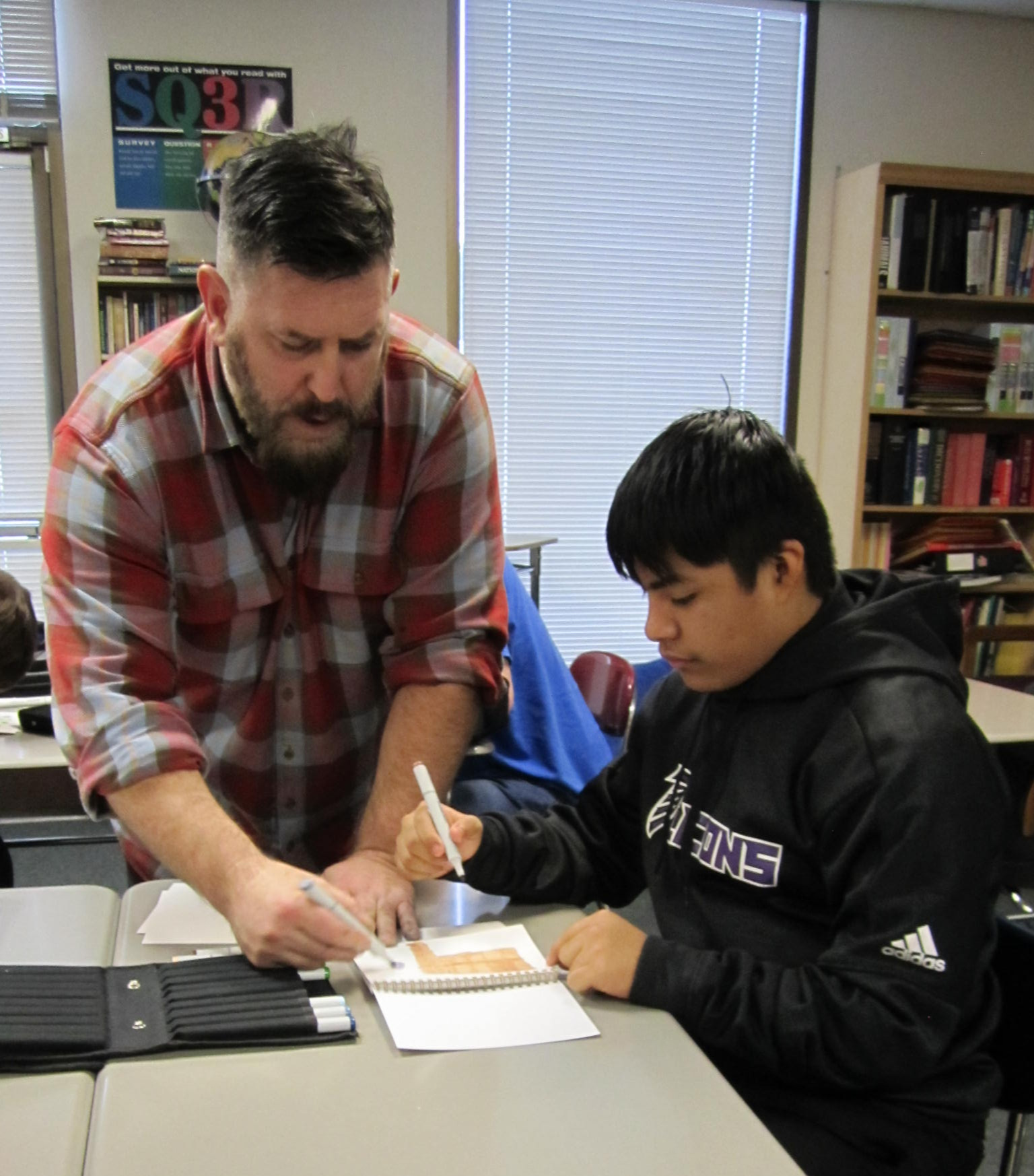 Imagination International Graphic Artist Matt Brundage shows some of his drawing techniques to Center Point students.
