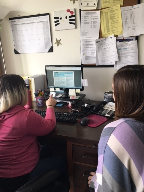 A program participant conducts research with an Independent Living Skills staff member close by should they need assistance.